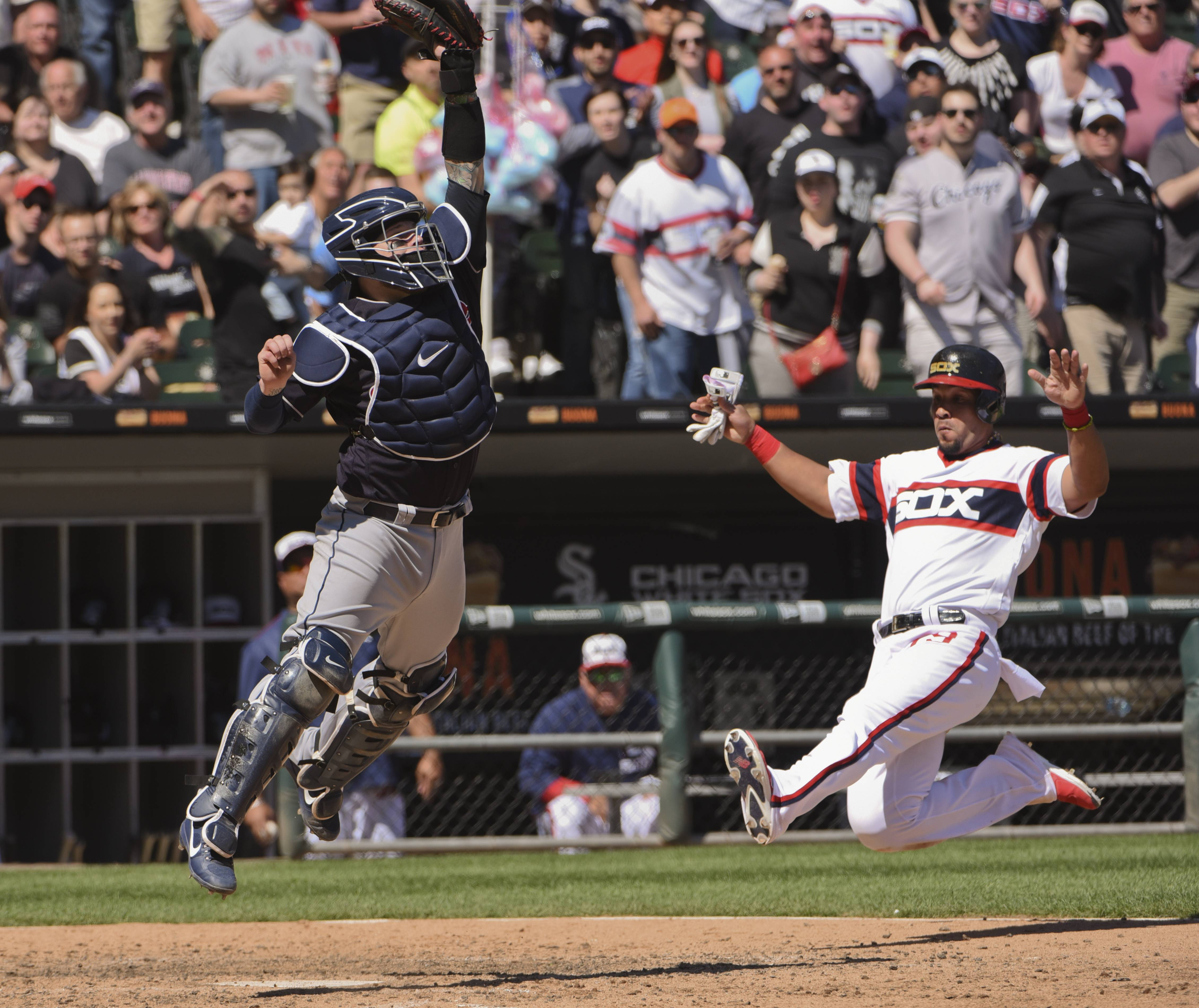 Cleveland Indians catcher Roberto Perez leaps to catch the ball as Chicago White Sox's Jose Abreu scores on an RBI-double hit by Avisail Garcia during the fifth inning of the game in Chicago Sunday.