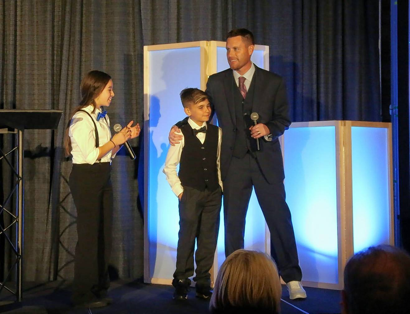 Curt McReynolds, CEO and president of the Boys & Girls Clubs of Dundee Township, stands with club members on stage at an annual fundraising event, the Tennies and Ties Gala. McReynolds is leaving May 19 to take a new role at the Boys & Girls Clubs of Greater Scottsdale.