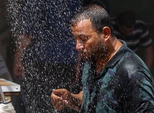An Iraqi man cools off the summer heat by using an open air shower in Baghdad, Iraq. Most people on Earth have already felt extreme and record heat, drought or downpours goosed by man-made global warming, a new study finds.