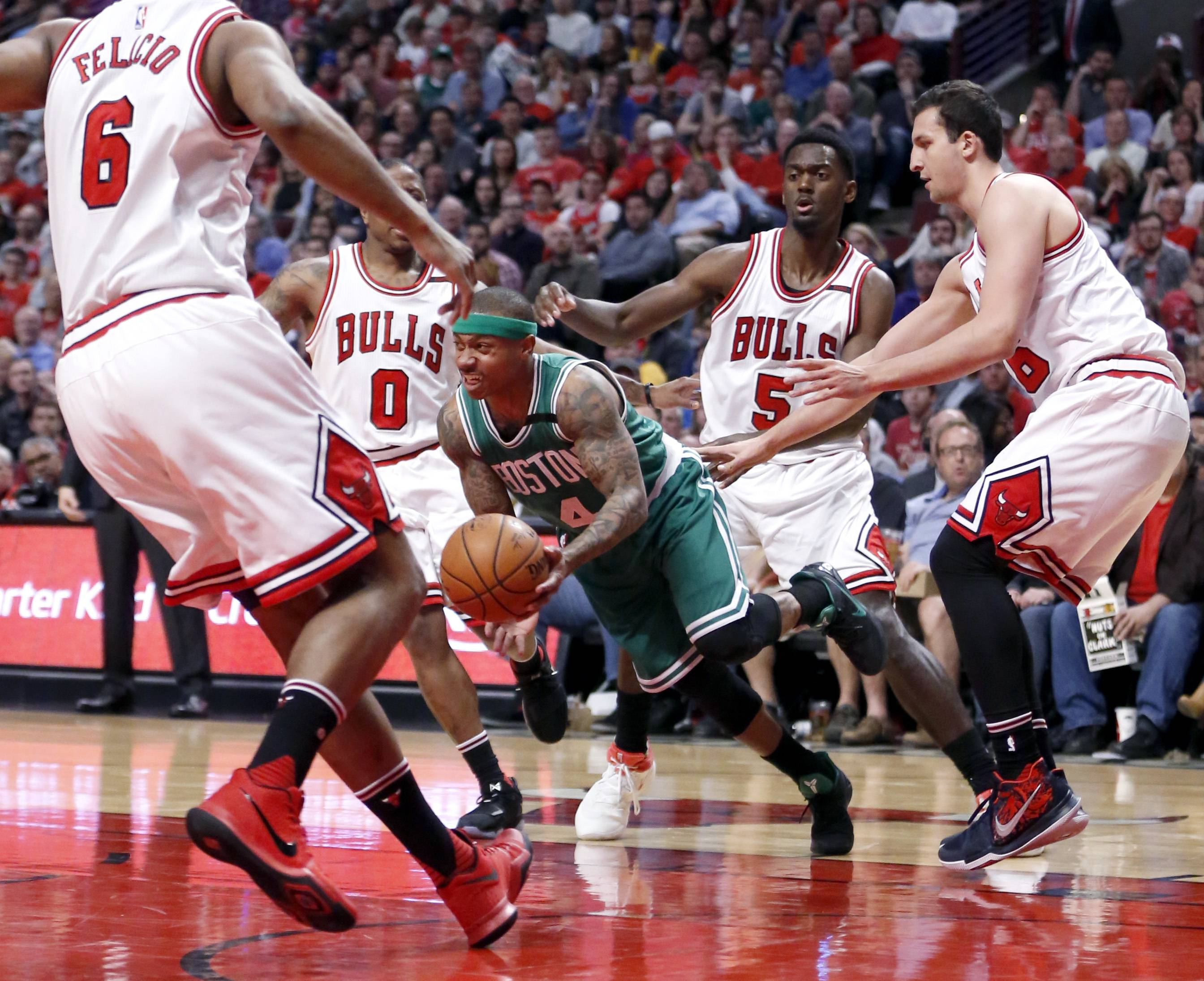 Boston Celtics' Isaiah Thomas (4) dribbles through the Chicago Bulls defense of Cristiano Felicio (6) Isaiah Canaan (0) Bobby Portis (5) and Paul Zipser during the first half in Game 4 of an NBA basketball first-round playoff series in Chicago, Sunday, April 23, 2017. (AP Photo/Charles Rex Arbogast)