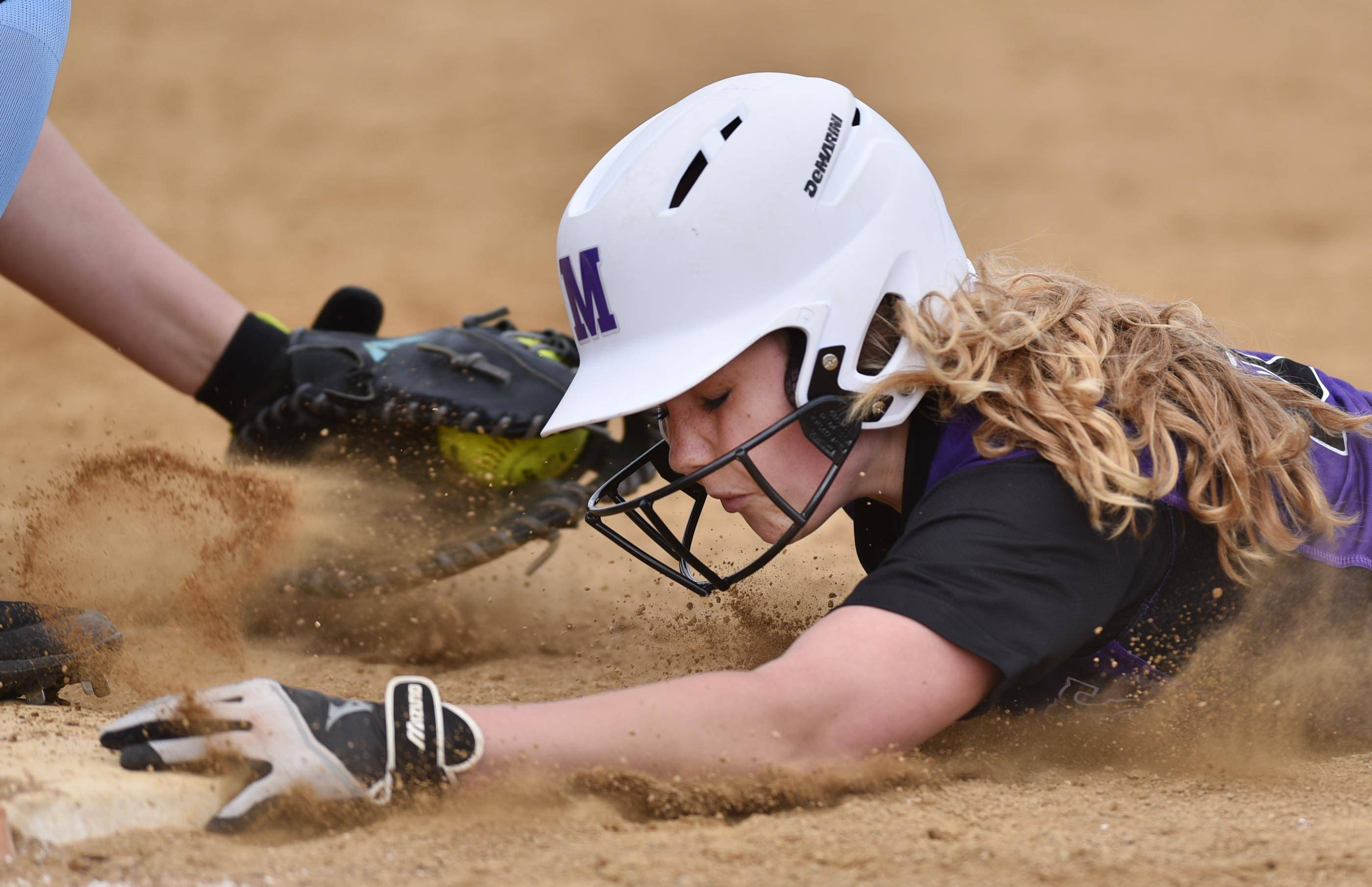 Rolling Meadows baserunner Emily Schmidt dives safely back under the tag of Prosect first baseman Colleen Palczynski Thursday at Rolling Meadows.