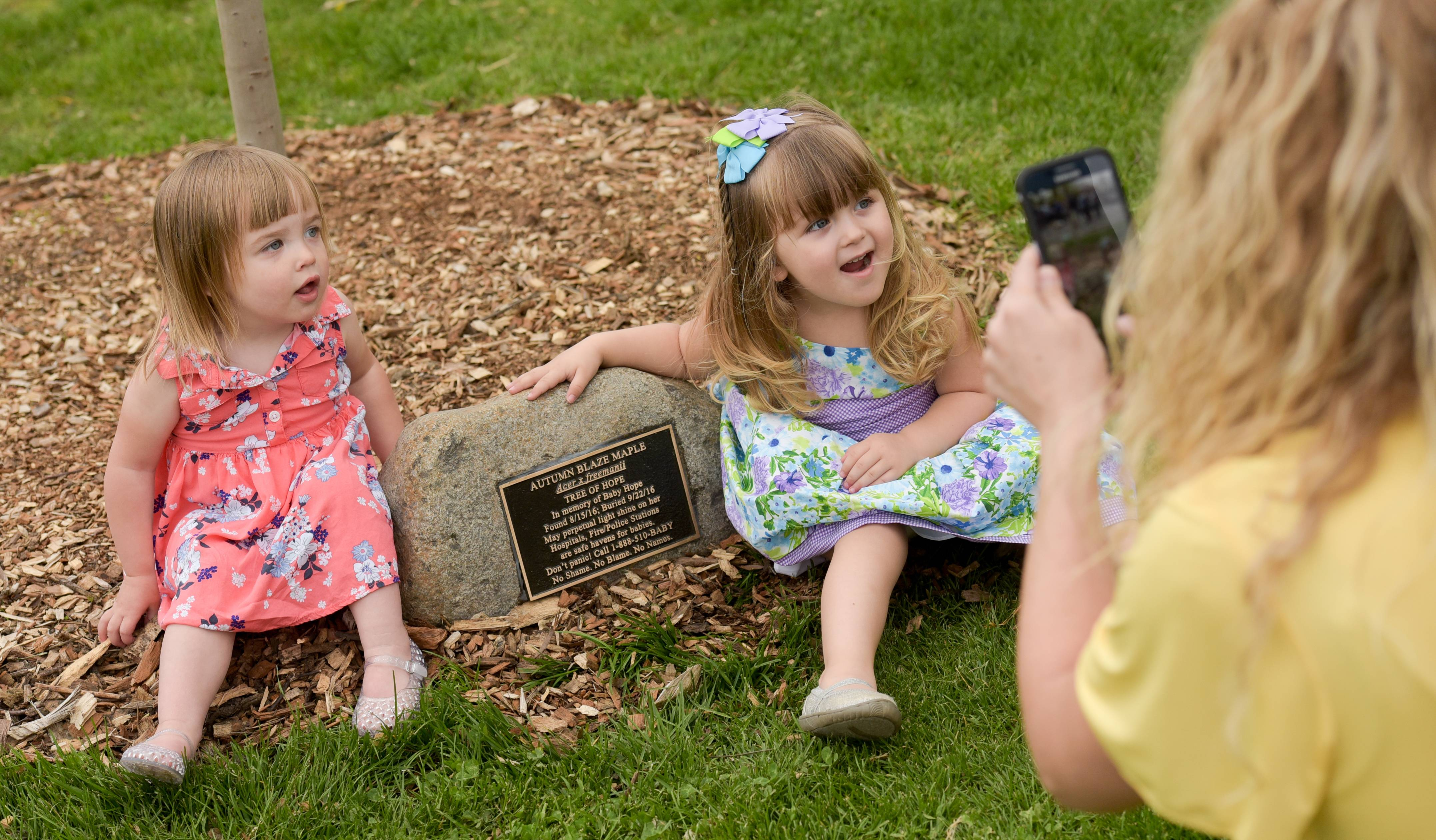 "Roselle mom Christie Haack snaps pictures of two ""safe haven babies,"" Zoe Wituk, 2, of St. Charles and her own adopted daughter Trinity, 2, in front of a plaque and tree in memory of Baby Hope, who was found dead last August in a backpack."