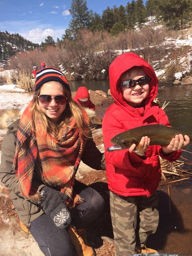 Au pair Julia Brockmeyer and Finn Donehoo, 6, show off a fish they caught in Denver.