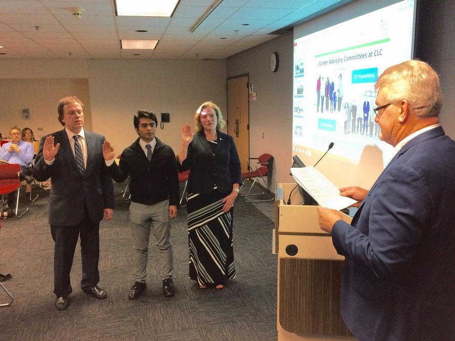 College of Lake County board Chairman Richard Anderson, foreground, swears in newly elected trustee Matthew Stanton, left, new student trustee Hansel Lopez, center, and new trustee Catherine Finger at a meeting Tuesday night in Grayslake.