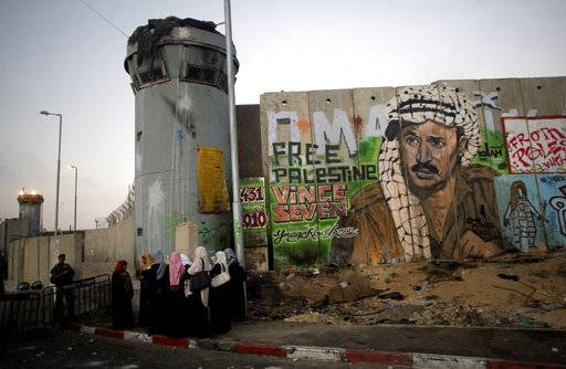 File - In this Friday, Aug. 13, 2010 file photo, Palestinian women wait near a section of Israel's separation barrier covered in graffiti, one depicting the late Palestinian leader Yasser Arafat, at the Qalandiya checkpoint , between Jerusalem and the West Bank city of Ramallah. Israel began construction of its 150-mile (250-kilometer) separation barrier in 2002 in response to a wave of Palestinian suicide bombings. Israel says the structure is a defense measure. But because it frequently juts into occupied West Bank land, the Palestinians see it as a land grab that poses an obstacle to their dream of establishing an independent state. (AP Photo/Sebastian Scheiner, File)