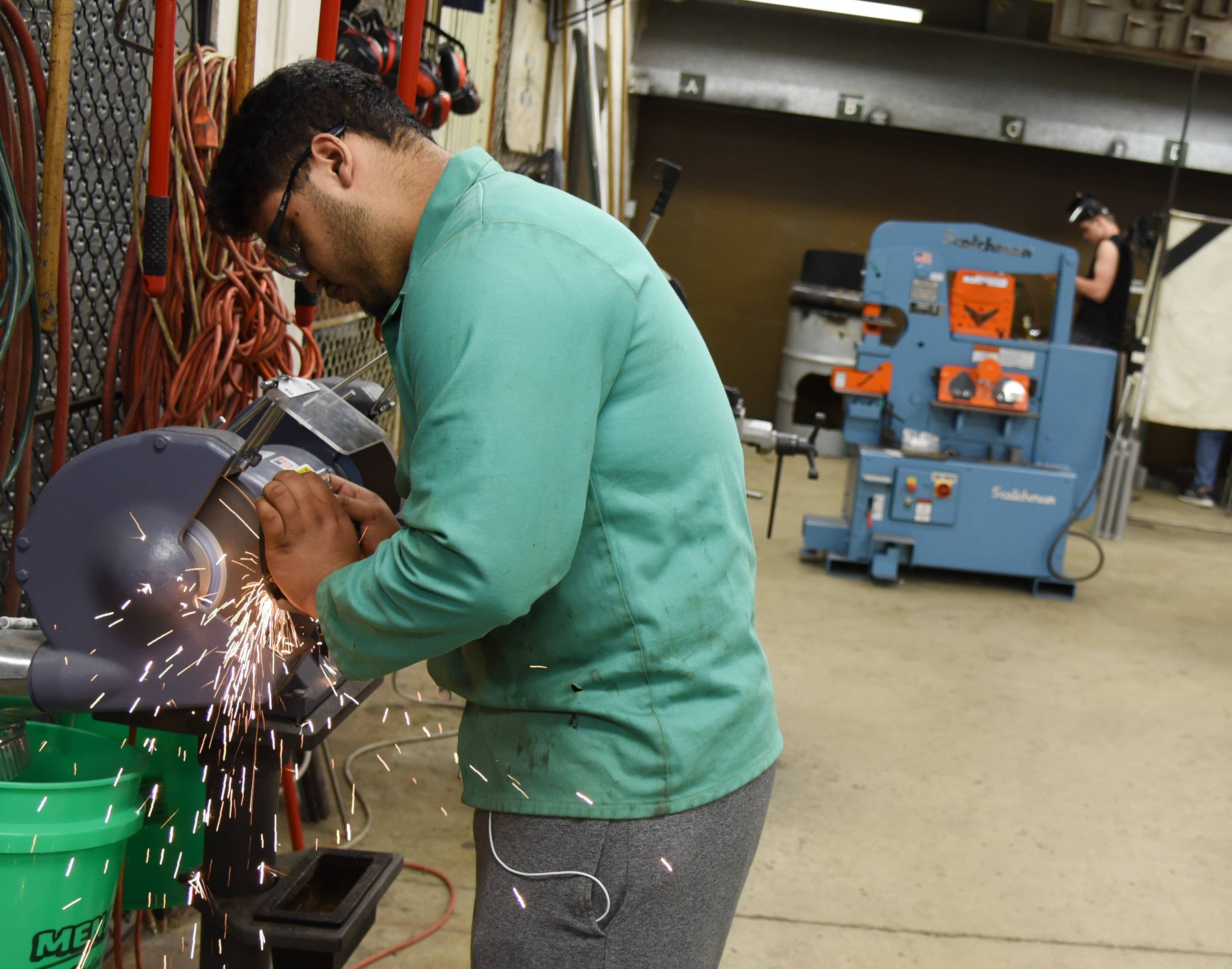 Junior Gabriel Martinez grinds a piece of metal during a welding class Wednesday at Elgin High School.