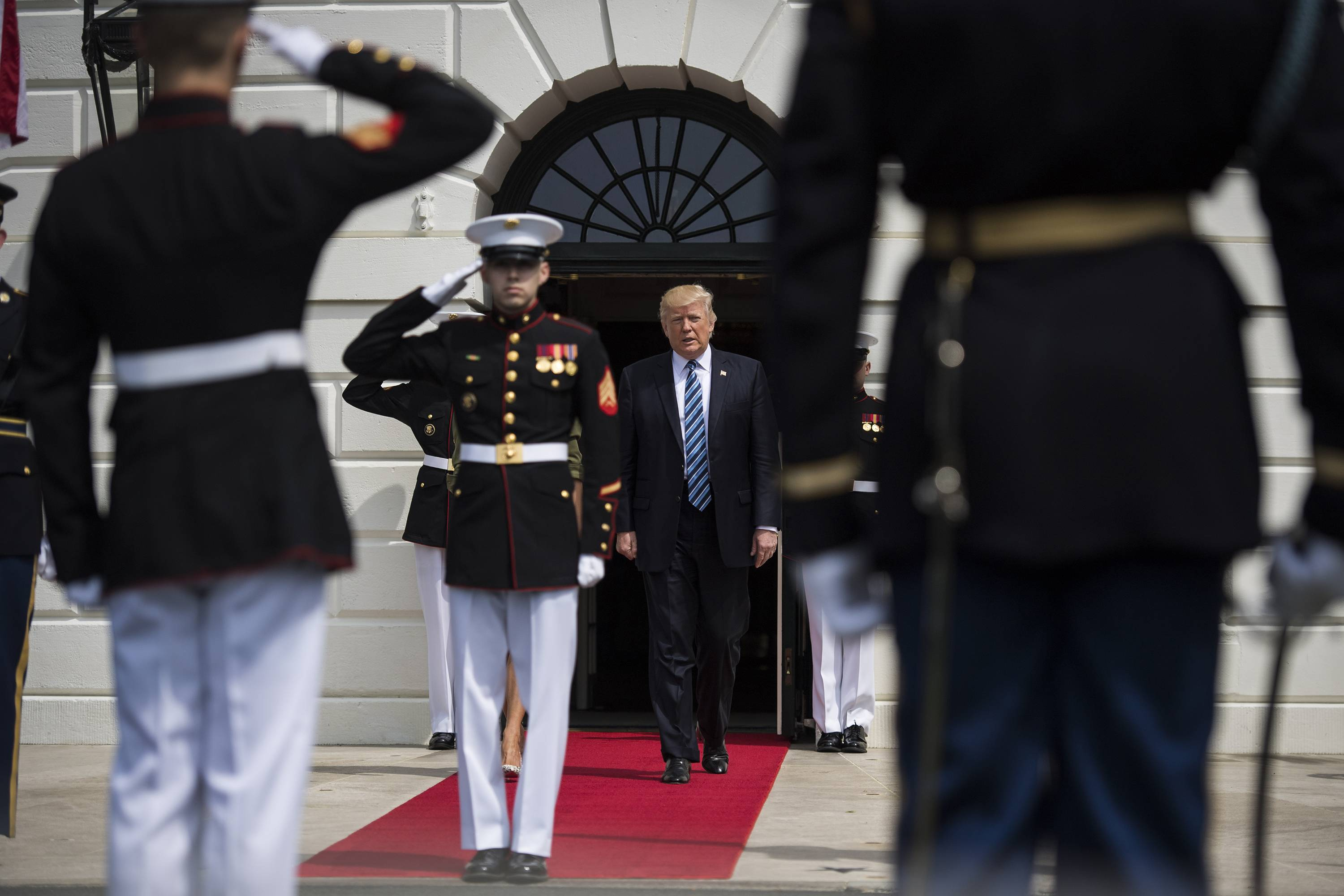 President Donald Trump walks out to greet Argentine President Mauricio Macri and his wife, Juliana Awada, at the White House on Thursday.