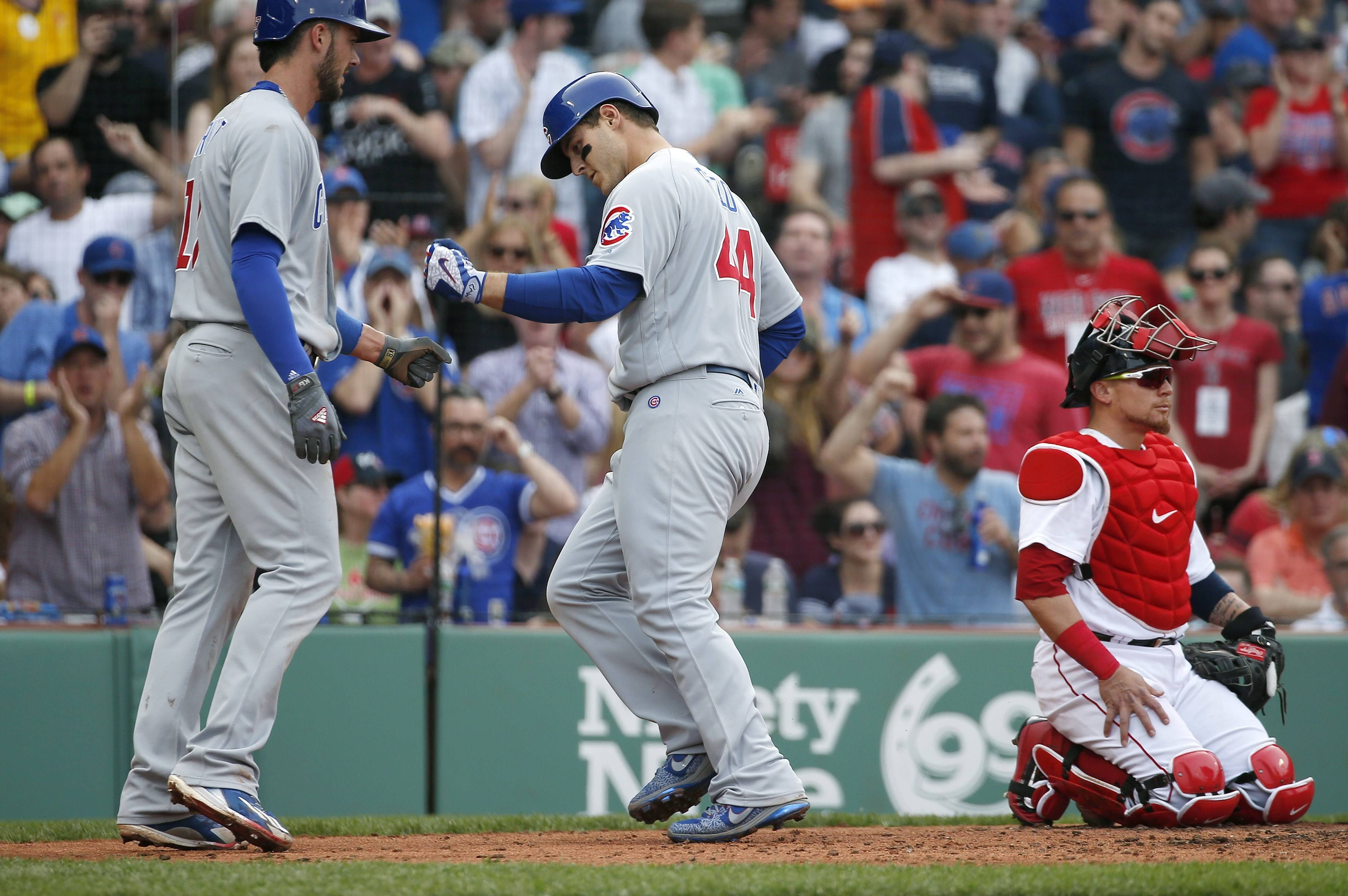 Chicago Cubs' Anthony Rizzo (44) celebrates his two-run home run that also drove in Kris Bryant, left, behind Boston Red Sox's Christian Vazquez, right, during the fourth inning of a baseball game, Saturday in Boston.