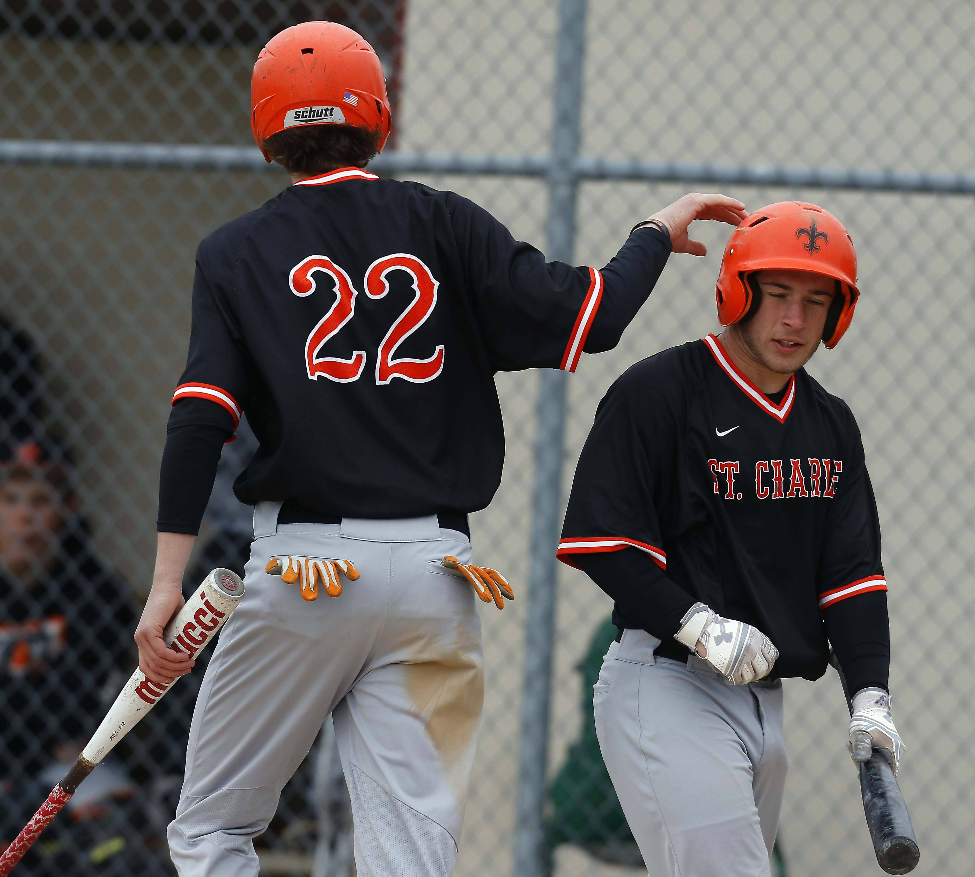 St. Charles East's Niko Klebosits, left, is greeted by Nico Piaskowy after crossing the plate on an RBI single by Cole Conn Saturday during baseball in Aurora.