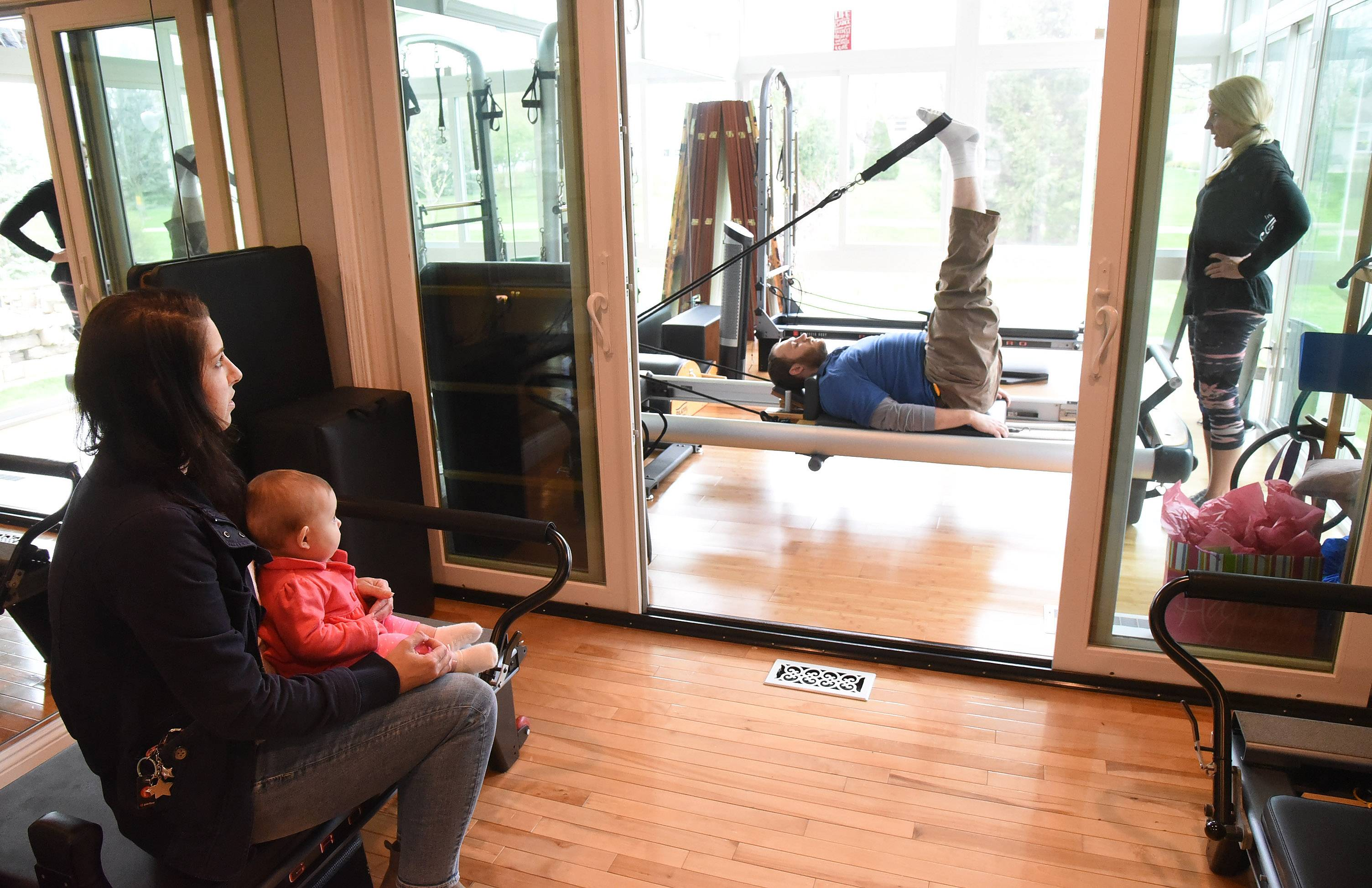"James ""J.D."" DeBouver works out with his mom Susan DeBouver at her Pilates Plus studio in Schaumburg, while wife Jennifer and daughter Nina watch."