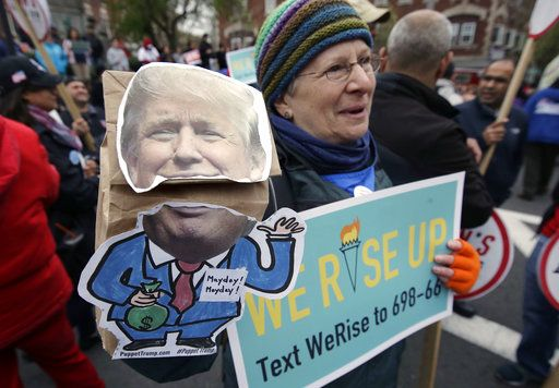 Nancy Kohn, of Boston, holds a Donald Trump puppet and a placard during a May Day rally, Monday, May 1, 2017, in Chelsea, Mass. Thousands of people chanted, picketed and marched on cities across America on Monday as May Day demonstrations raged against President Donald Trump's immigration policies.