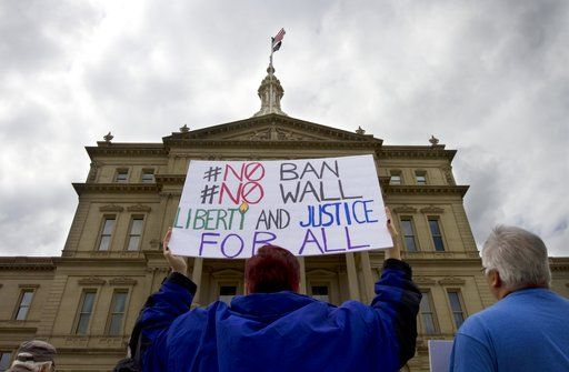Angela Patrick, 48, holds a sign above her head as she listens during a May Day rally at the state Capitol, Monday, May 1, 2017, in Lansing, Mich. Immigrant groups and their allies have joined forces to carry out marches, rallies and protests in cities nationwide next week to mark May Day, saying there's renewed momentum to fight back against Trump administration policies.