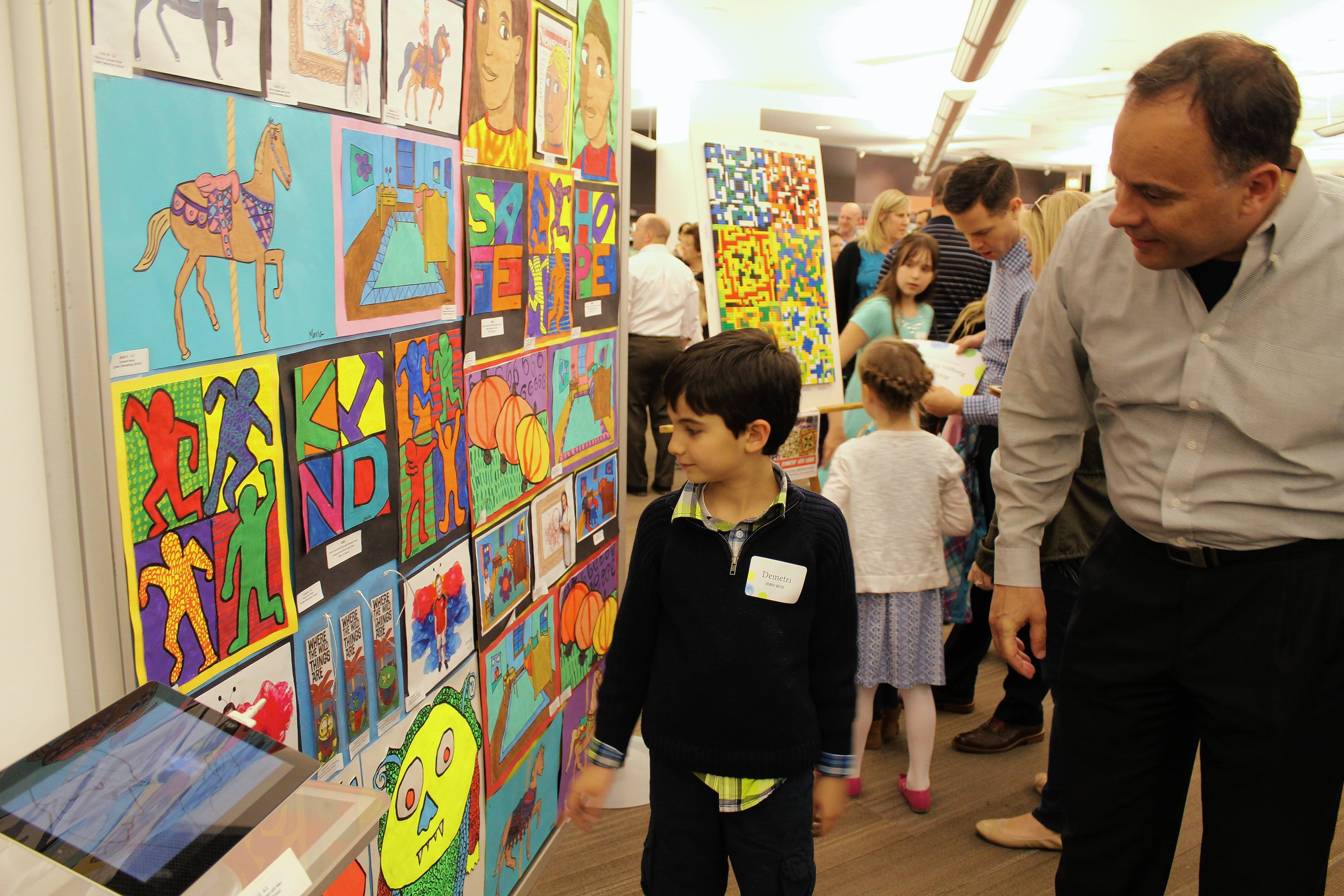 One of the student artists in the annual District 25 art show admires a display at the Arlington Heights Memorial Library. Some 400 students in grades K-8 have their artwork in the exhibition.