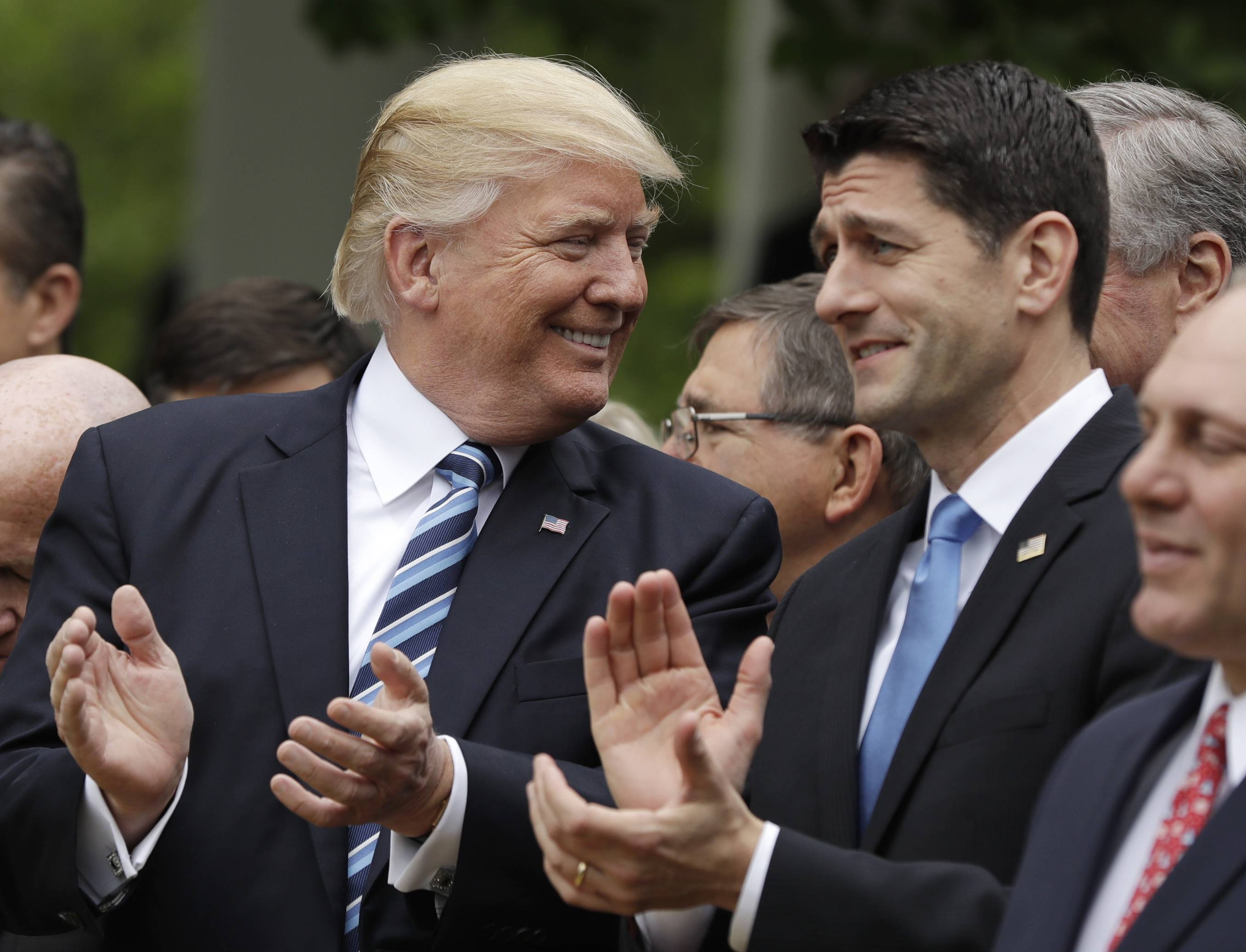 President Donald Trump talks with House Speaker Paul Ryan in the White House Rose Garden after the GOP pushed a health care bill through the House.