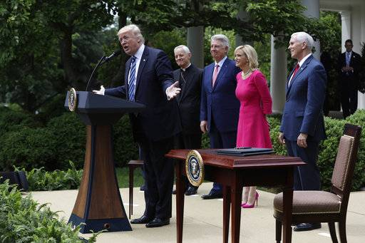 President Donald Trump speaks in the Rose Garden of the White House in Washington, Thursday, May 4, 2017, before signing an executive order aimed at easing an IRS rule limiting political activity for churches. From second from left are, Cardinal Donald Wuerl is the Archbishop of Washington, Pastor Jack Graham, Paula White, senior pastor of New Destiny Christian Center in Apopka, Fla. and Vice President Mike Pence.