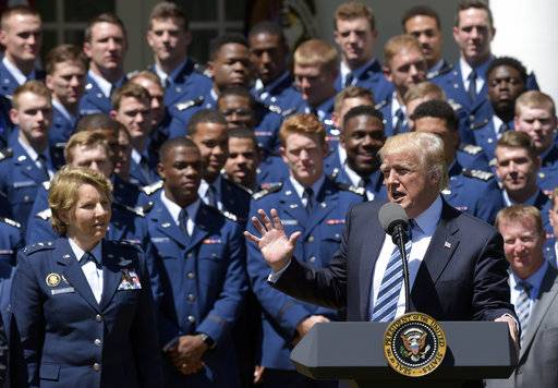Air Force Academy Superintendent Lt. Gen. Michelle Johnson, left, and football team members, listens as President Donald Trump speaks in the Rose Garden of the White House in Washington, Tuesday, May 2, 2017, during a presentation ceremony of the Commander-in-Chief trophy to the Air Force Academy football team.