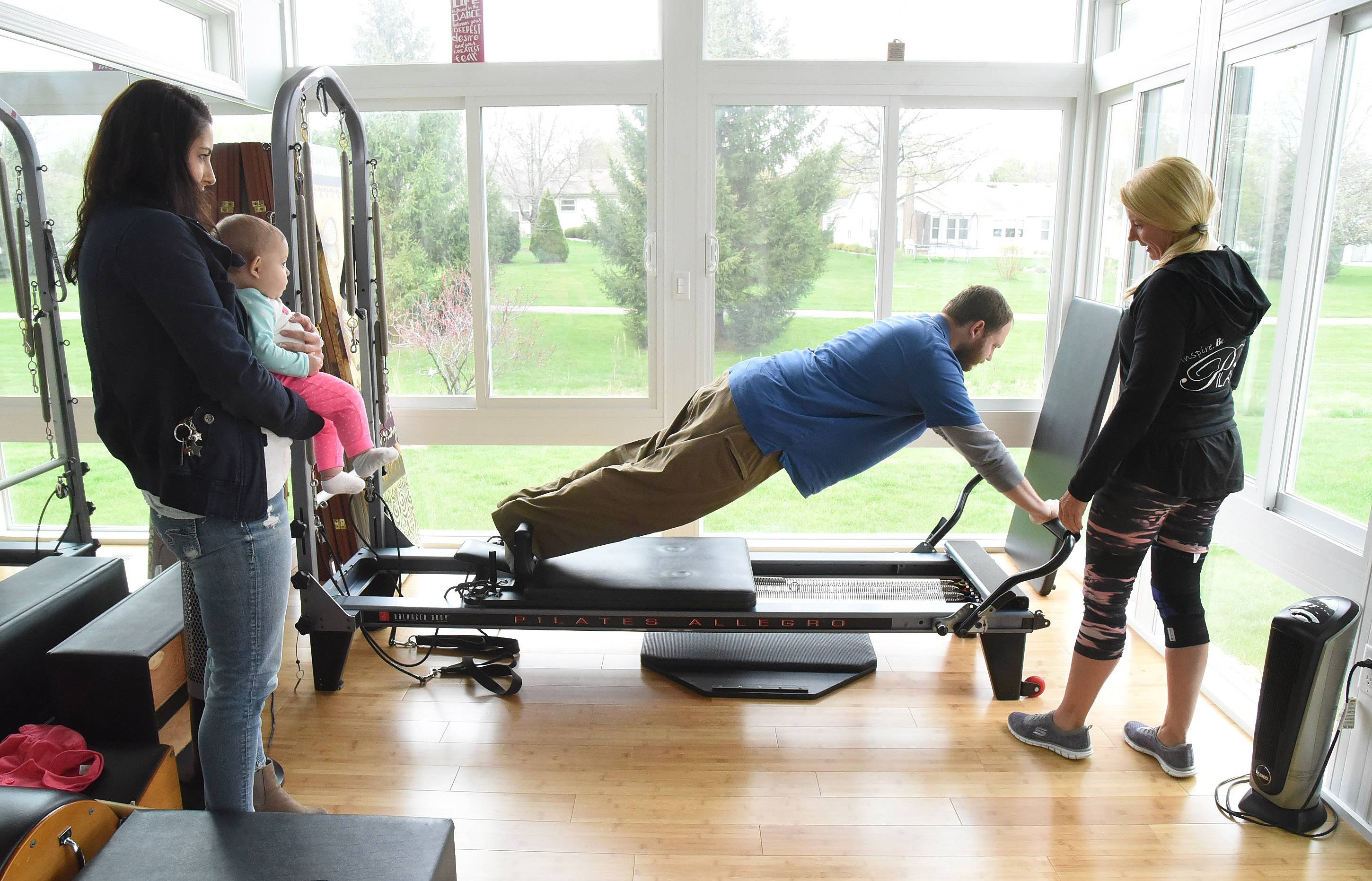"James ""J.D."" DeBouver works out with his mom, Susan DeBouver, at her Pilates Plus studio in Schaumburg. His wife, Jennifer, and daughter, Nina, watch."