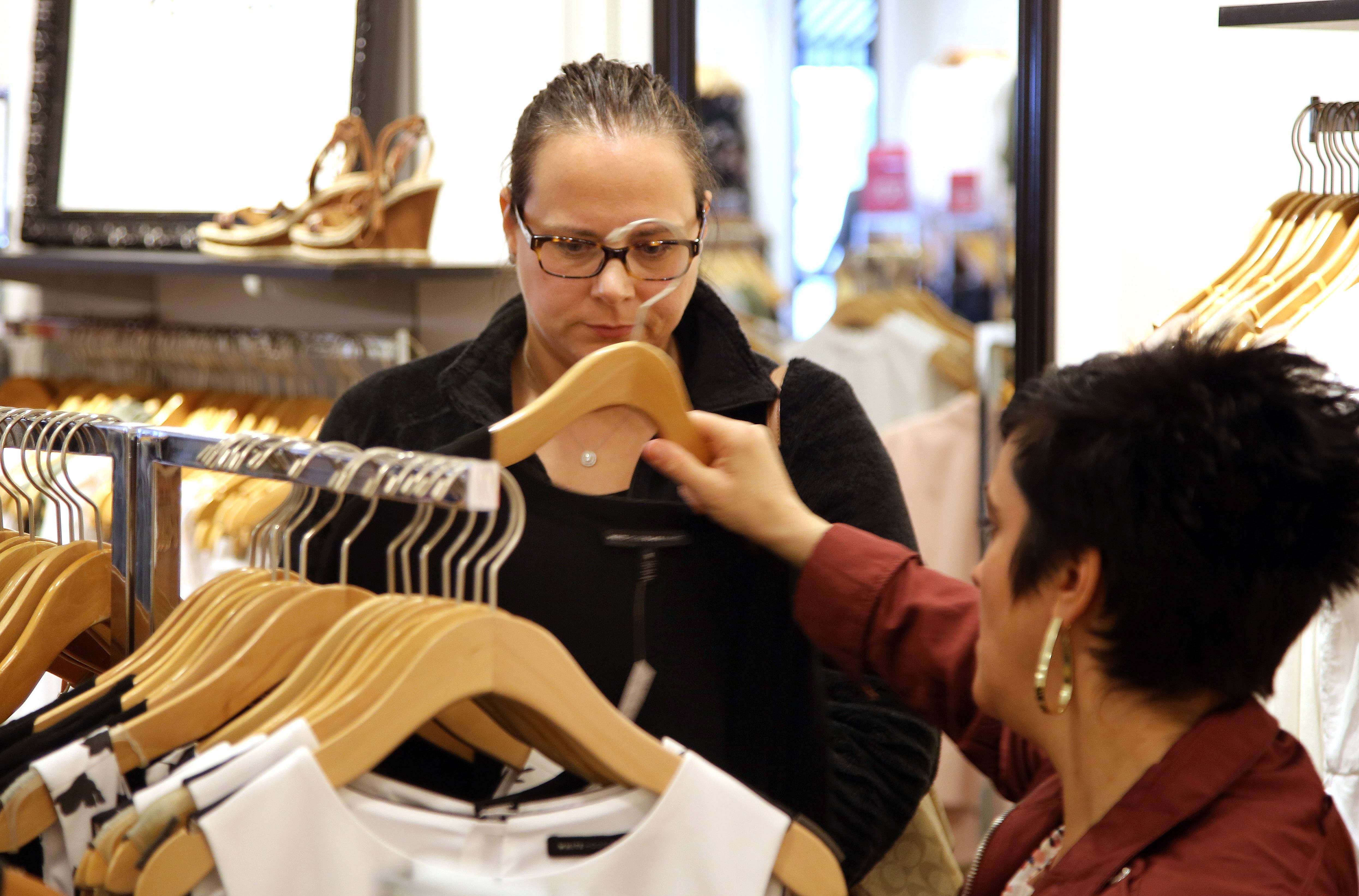 Fittest Loser contestant Penny Brown of Fox Lake, left, picks out clothes with sales person Adriana Rago at White House-Black Market in Deer Park Town Center.