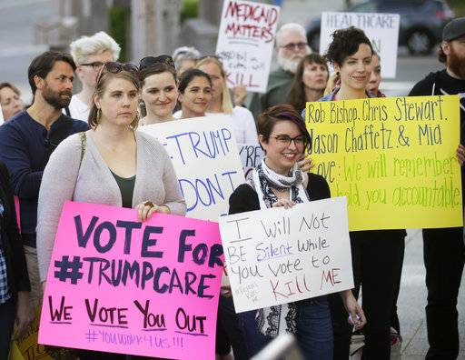 FILE - In this Thursday, May 4, 2017 file photo, demonstrators hold signs during a healthcare rally in Salt Lake City. Utah's all-Republican House delegation voted Thursday in favor of a health care overhaul that could impact people with pre-existing conditions, triggering serious worries from people who fit that category.