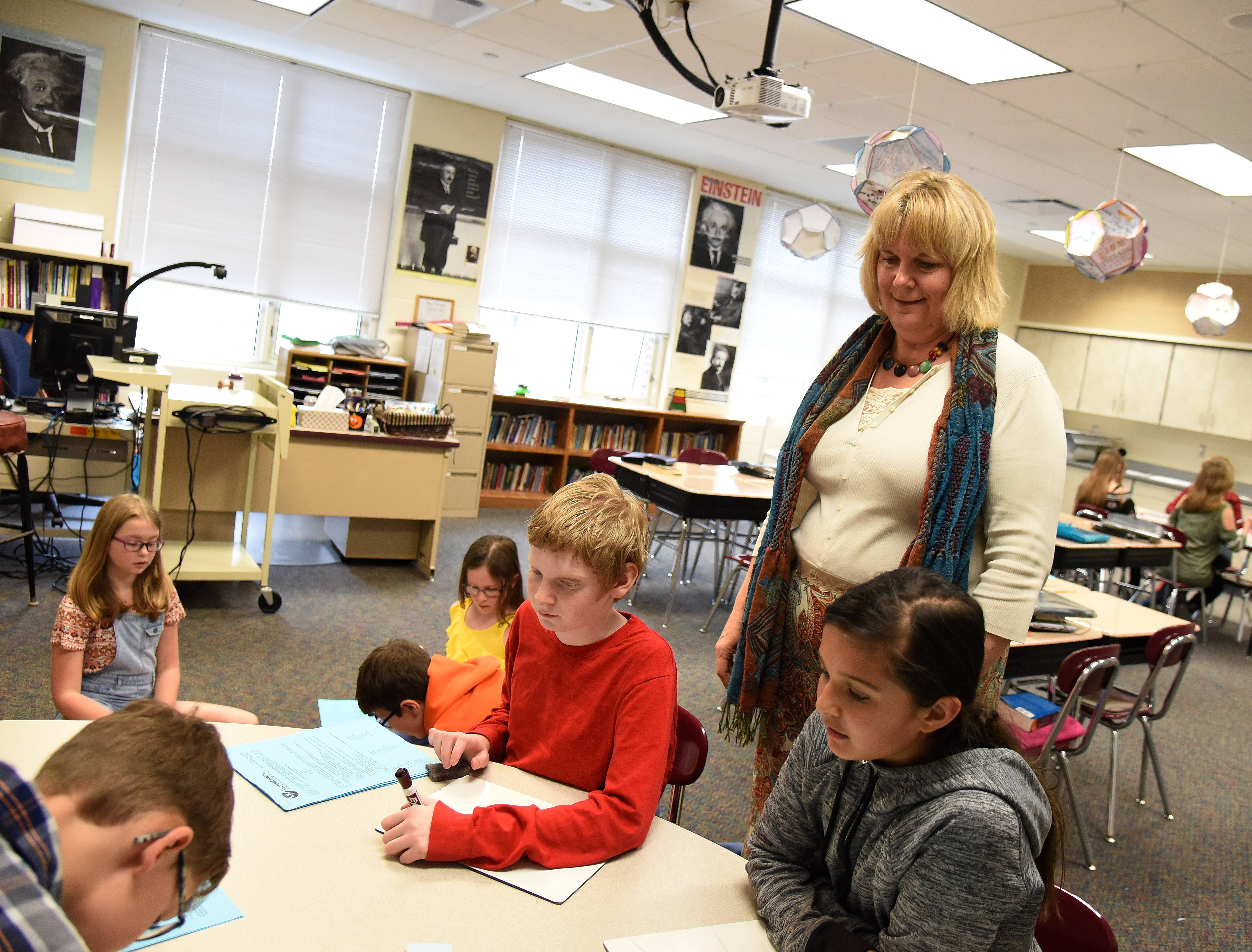Nancy Krasinski checks on the progress of her fifth-graders, who are playing Pictionary as part of an accelerated/enrichment classroom at Williamsburg Elementary School in Geneva.