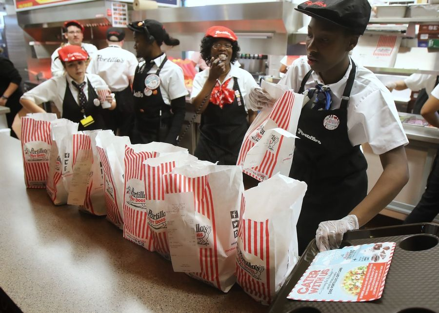 Restaurant employees hand out food orders during the grand opening last November of the new Portillo's restaurant in Deerfield.