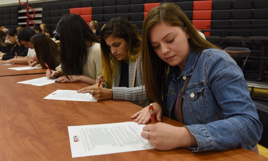 Wheeling High School juniors Chloe Cordle, front, and India Patel are among the 110 Northwest Suburban High School District 214 students signing letters of intent to become teachers as part of an Educator Prep event Thursday at Forest View Education Center in Arlington Heights.