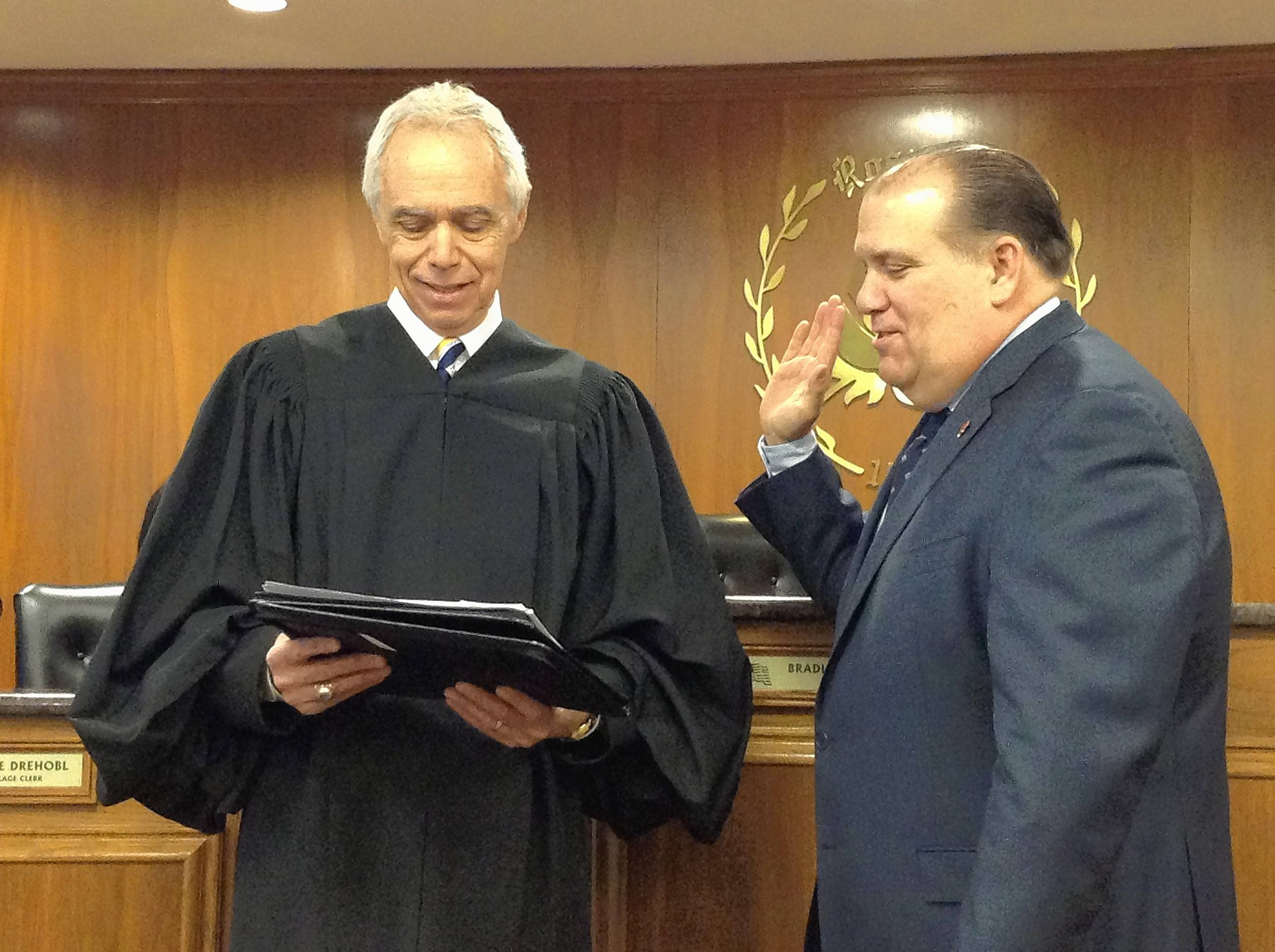Rosemont Mayor Brad Stephens, right, is sworn into his third full 4-year term Wednesday by Illinois Court of Claims Judge Don Storino. Starting with the new term, Stephens is getting a 53 percent raise.