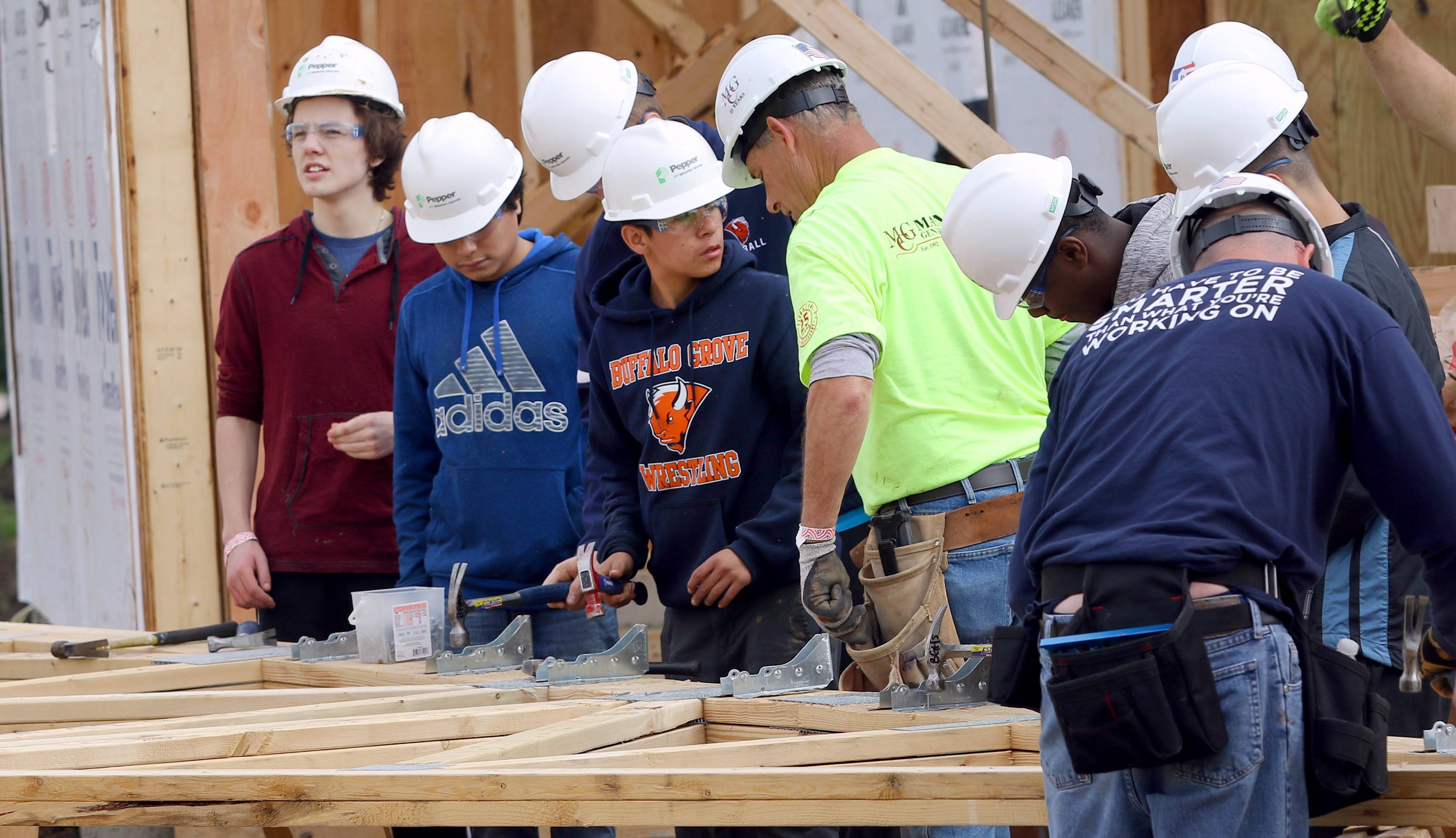 Northwest Suburban High School District 214 students were among volunteers who began building a house Thursday in Spring Grove for Army veteran Tony Chobanov of Naperville.