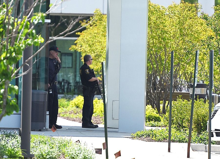 Police with weapons stand outside the emergency department at Delnor Hospital in Geneva Saturday.
