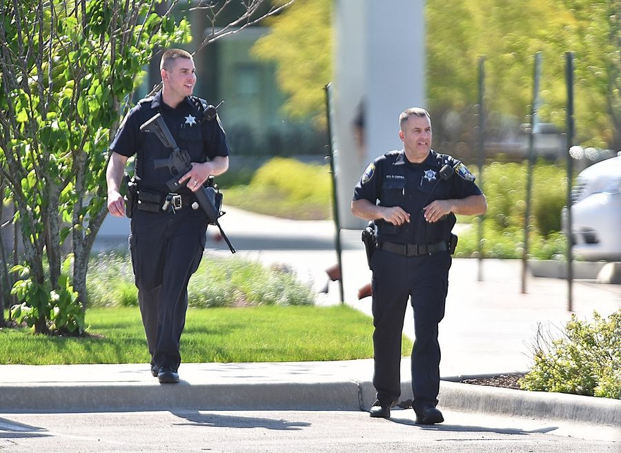 Two police officers walk to escort employees to their cars in the parking lot of Delnor Hospital in Geneva Saturday while a hostage situation takes place inside.