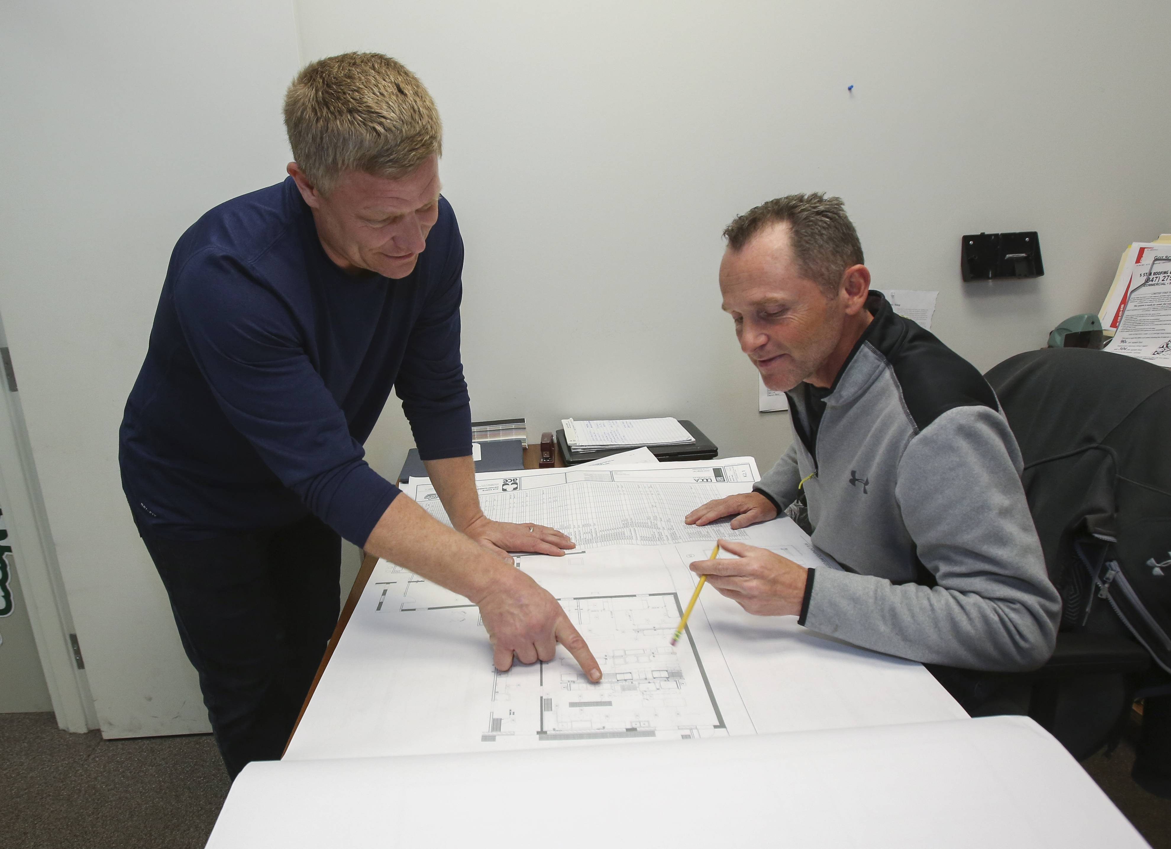 Mark Hoffmann, co-owner of Ala Carte Entertainment in Schaumburg, left, goes over plans for a new restaurant with Brian Campbell, right.