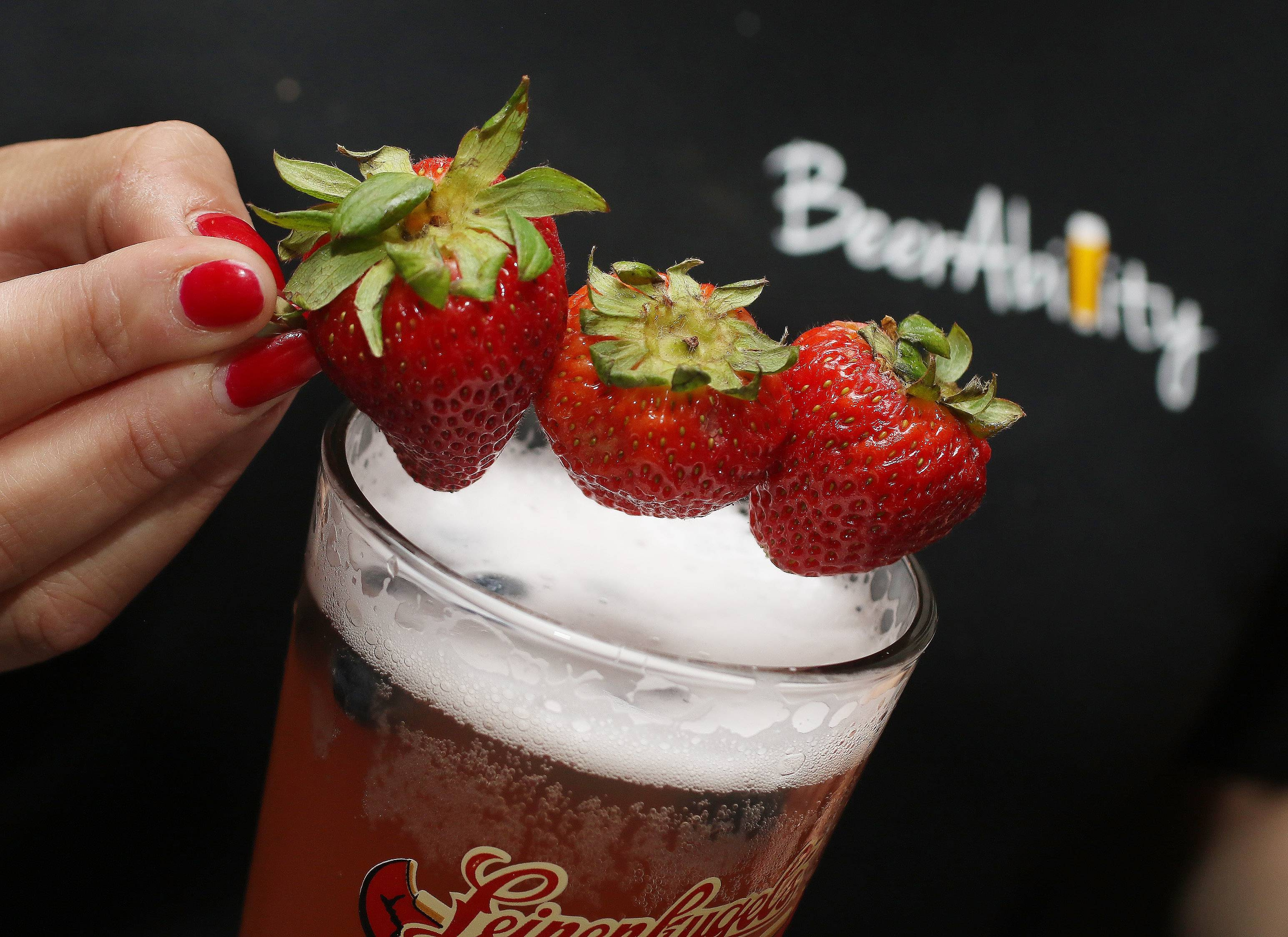 A strawberry garnish is added to the Mixed Berry Summer Shanty at BeerAbility pub in Round Lake Heights. The drink is made with mixed berry juice, Summer Shanty with frozen blueberries and strawberries.