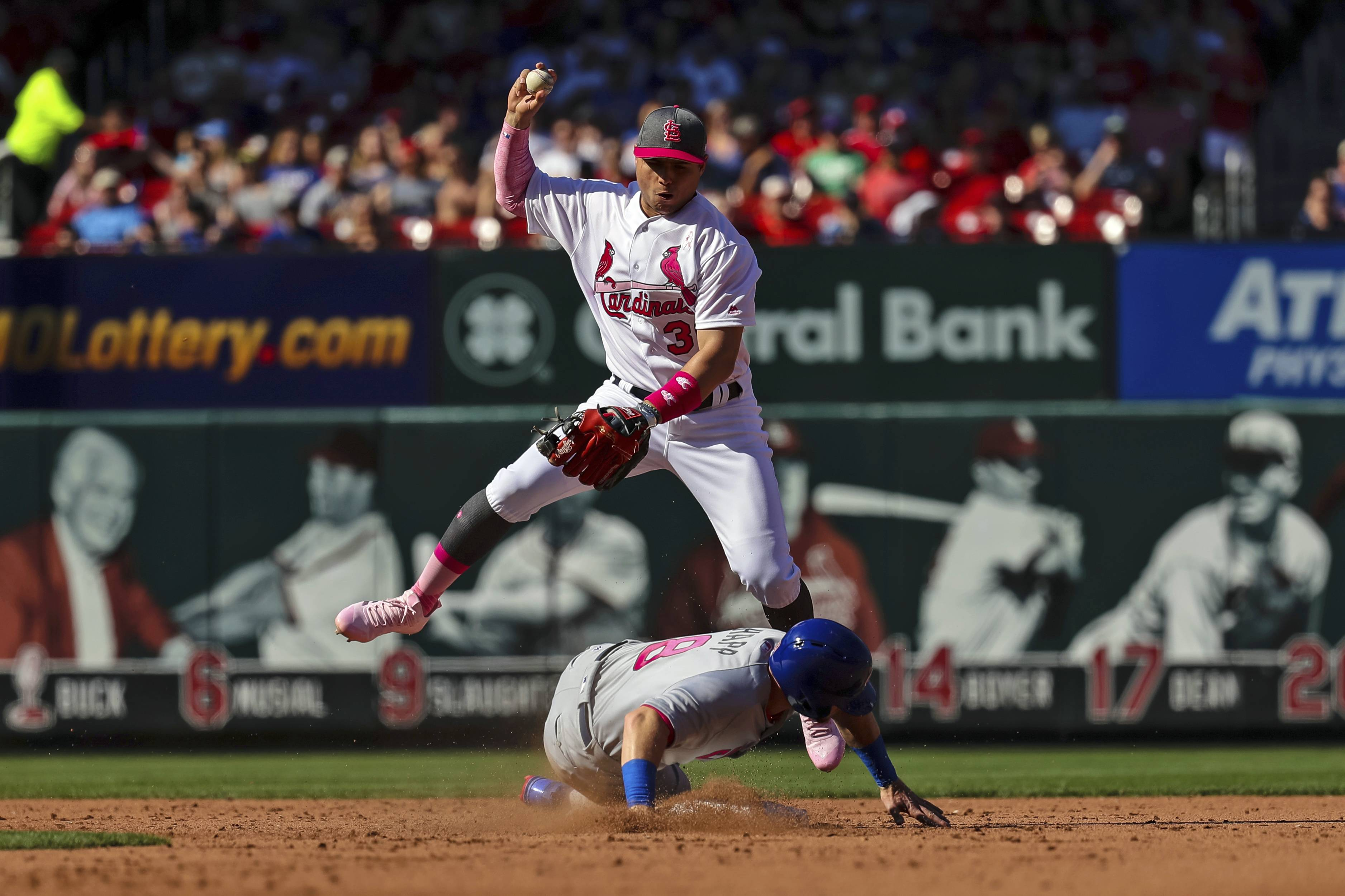 St. Louis Cardinals shortstop Aledmys Diaz, top, leaps into the air as Chicago Cubs' Ian Happ, bottom, slides in to break up a double play in the fifth inning of a baseball game, Saturday, May 13, 2017, in St. Louis. The Cubs' Anthony Rizzo was called out at first due to slide interference by Happ,