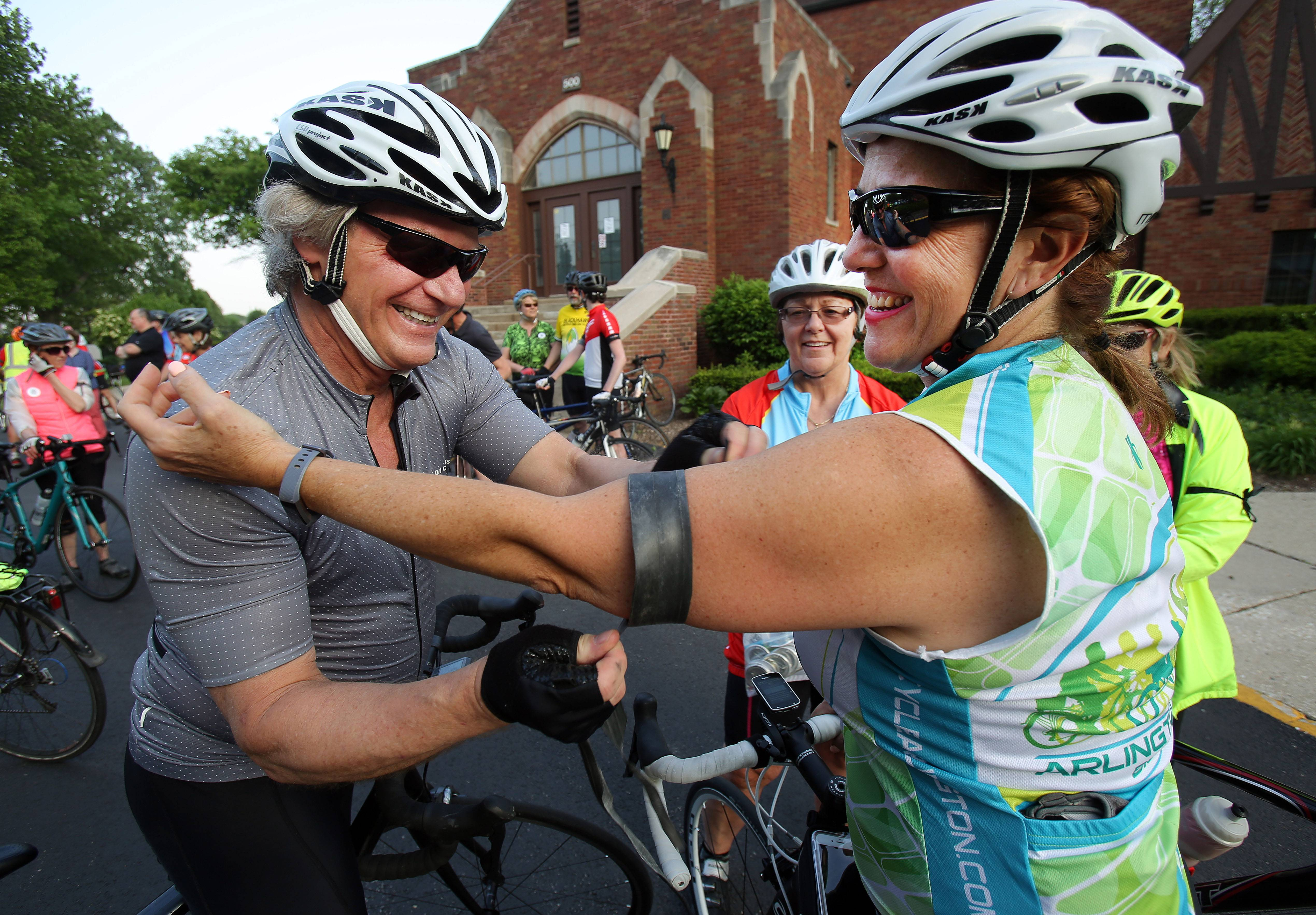 Don Sortor, of Arlington Heights, puts a black armband made of old inner tube on Tara Riley, also of Arlington Heights, on Wednesday. Both are members of the Arlington Heights Bicycle Club who participated in the International Ride of Silence in honor of Mount Prospect cyclist Jodi Beaudry. Beaudry died on June 9, 2016, after being struck by an SUV.