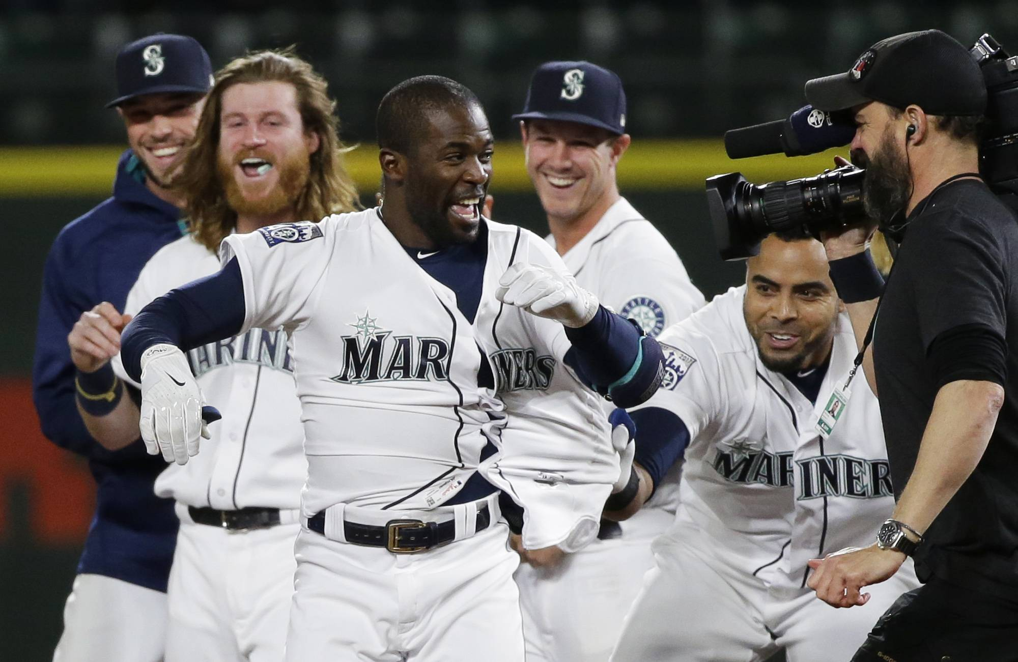 Seattle Mariners' Guillermo Heredia, front, has his jersey tugged by teammate Nelson Cruz, right, after Herdia hit a walk-off RBI single to score Jarrod Dyson and give the Mariners a 5-4 win over the Chicago White Sox in a baseball game, Thursday, May 18, 2017, in Seattle.