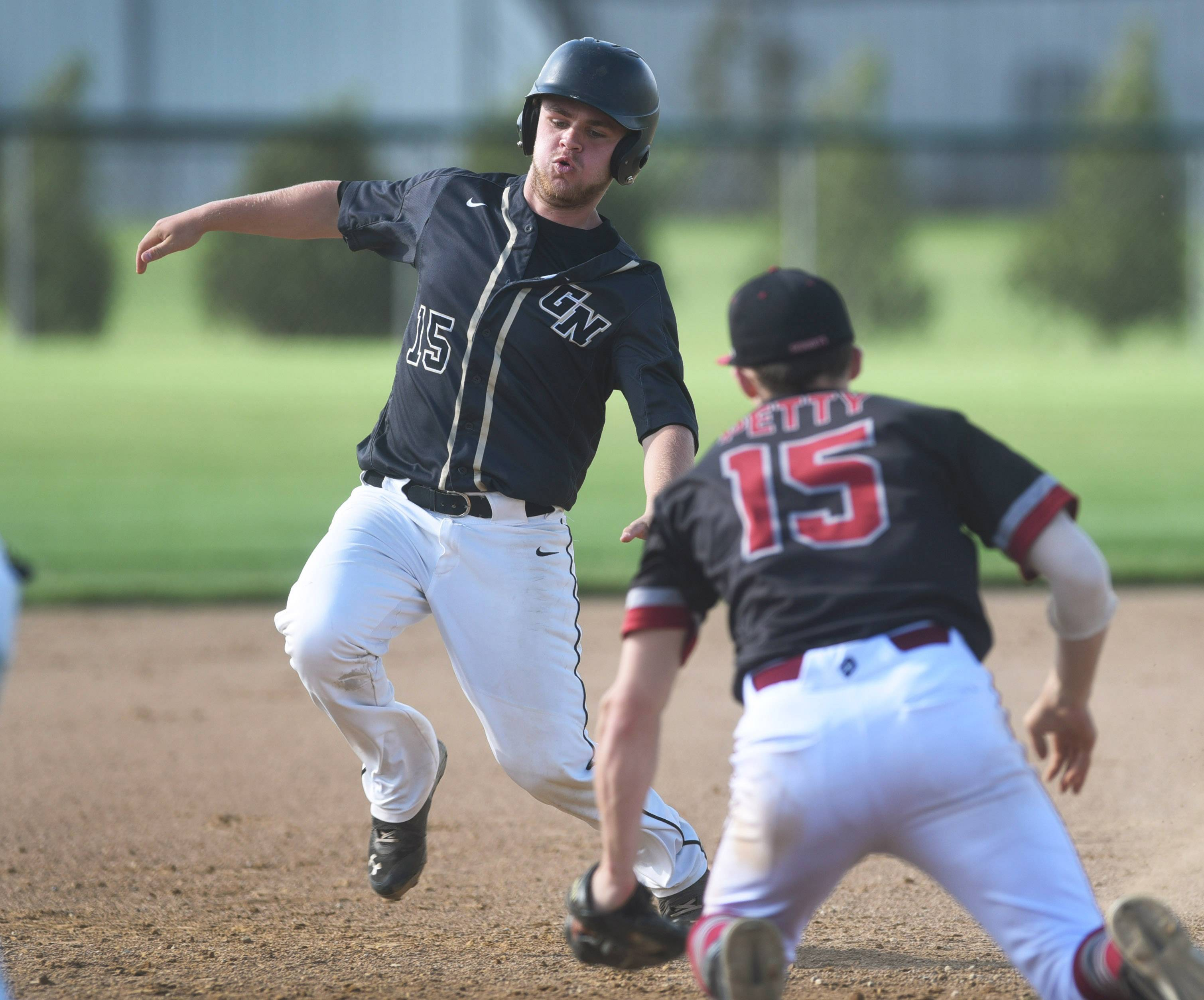 Grayslake North's Regen Marsell (15) begins his slide into third base but is tagged out by Antioch's John Petty (15) during Thursday's game at Antioch.