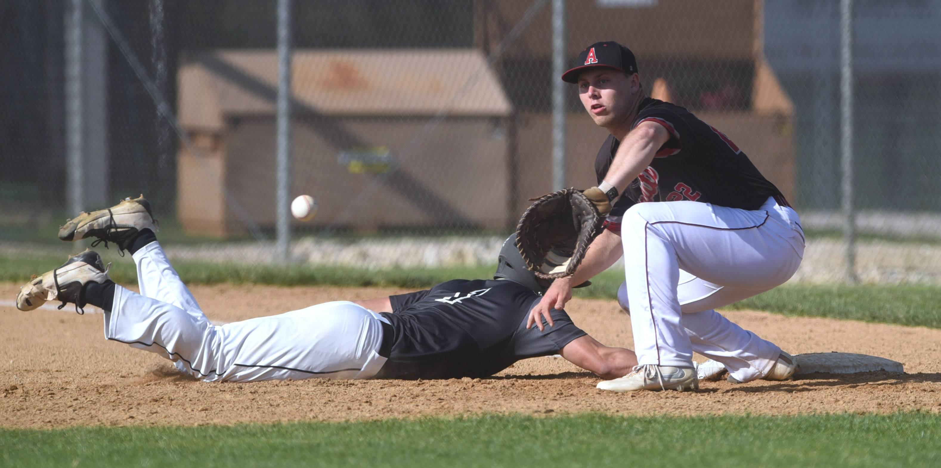Antioch first baseman Ben Gutke waits for the throw as Grayslake North's Charles Burr slides safely back into first base during Thursday's at Antioch.