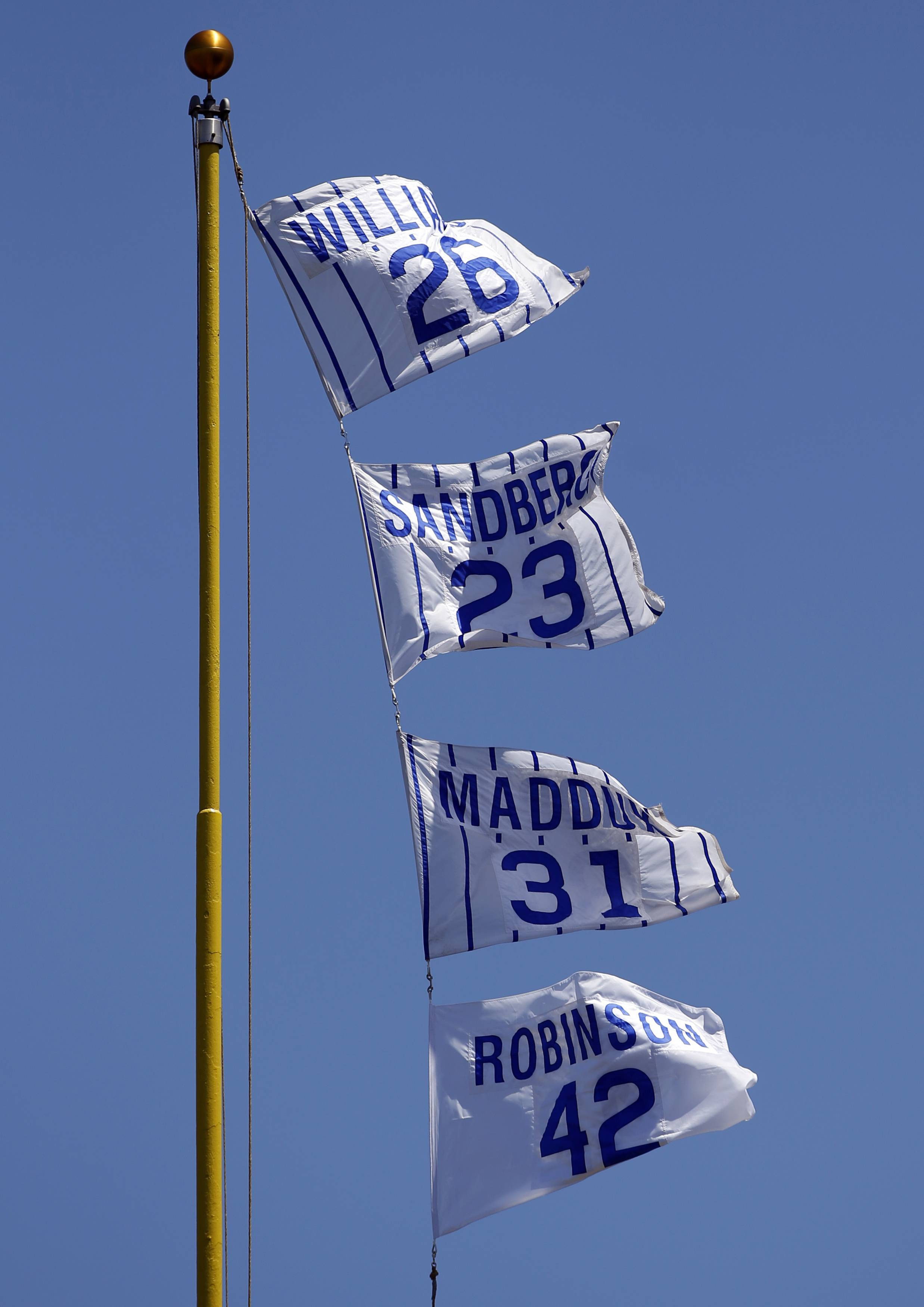 The Chicago Cubs raise a flag in honor of Jackie Robinson's (42) 70th anniversary of playing his first game at Wrigley Field, before a baseball game between the Cincinnati Reds and the Chicago Cubs in Chicago, Thursday, May 18, 2017.