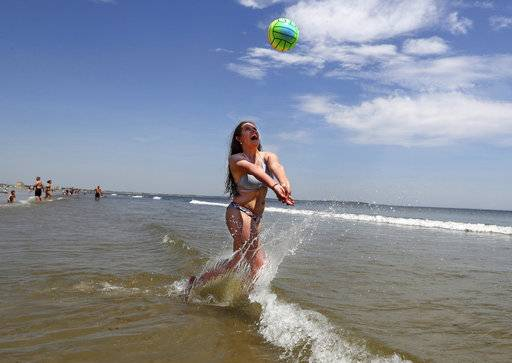 Nessa King of Wyndham, Maine, returns a shot while playing volleyball in record breaking heat at Old Orchard Beach, Maine, Thursday, May 18, 2017. King was one of hundreds of Maine high school seniors who skipped school to enjoy a day at the beach with classmates. (AP Photo/Robert F. Bukaty)