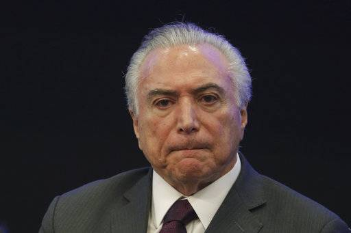 FILE - In this May 8, 2017, file photo, Brazil's President Michel Temer listens in during a event at the Brazilian Institute of Research in Brasilia, Brazil. Temer is denying a report that he endorsed the alleged bribing of a jailed former congressman to keep him quiet. The allegation made in a Globo News report on Wednesday, May 17, represents a potentially significant blow to President Temer. His administration has lurched from one crisis to another since he took office just over a year ago. (AP Photo/Eraldo Peres, File)