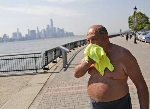 Ed Tirone takes a break from reading on the pier to wipe a wet washcloth over his face in Hoboken, N.J., Thursday, May 18, 2017. Forecasters say temperatures across the state could reach the above 90 degrees on Thursday and the trend is expected to continue through Friday. (AP Photo/Seth Wenig)