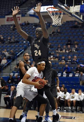 FILE - In this March 11, 2017, file photo, Central Florida's Tacko Fall (24) guards SMU's Ben Moore during the first half of an NCAA college basketball game in the American Athletic Conference tournament semifinals in Hartford, Conn. UCF's 7-foot-6 sophomore center Tacko Fall decided this spring to explore his NBA options, but all indications are he is finding out that his best option may be to return to school for another season. (AP Photo/Jessica Hill, File)