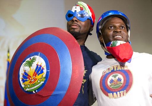 In this, Friday, May 19, 2017 photo, Haitian-American hip-hop star Wyclef Jean, left, poses with Captain Haiti, also known as Martin Nandy, after Nandy gave him a T-shirt and had him try on his outfit while Jean was speaking during a news conference at the Little Haiti Cultural Center in Miami. Jean performs Friday in Miami's Little Haiti, a community worried that the Trump Administration won't renew post-earthquake immigration benefits for roughly 50,000 Haitians.