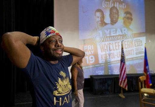 In this, Friday, May 19, 2017 photo, Haitian-American hip-hop star Wyclef Jean uses a small Haitian flag as a bandana as he prepares to speak during a news conference at the Little Haiti Cultural Center in Miami. Jean performs Friday in Miami's Little Haiti, a community worried that the Trump Administration won't renew post-earthquake immigration benefits for roughly 50,000 Haitians.