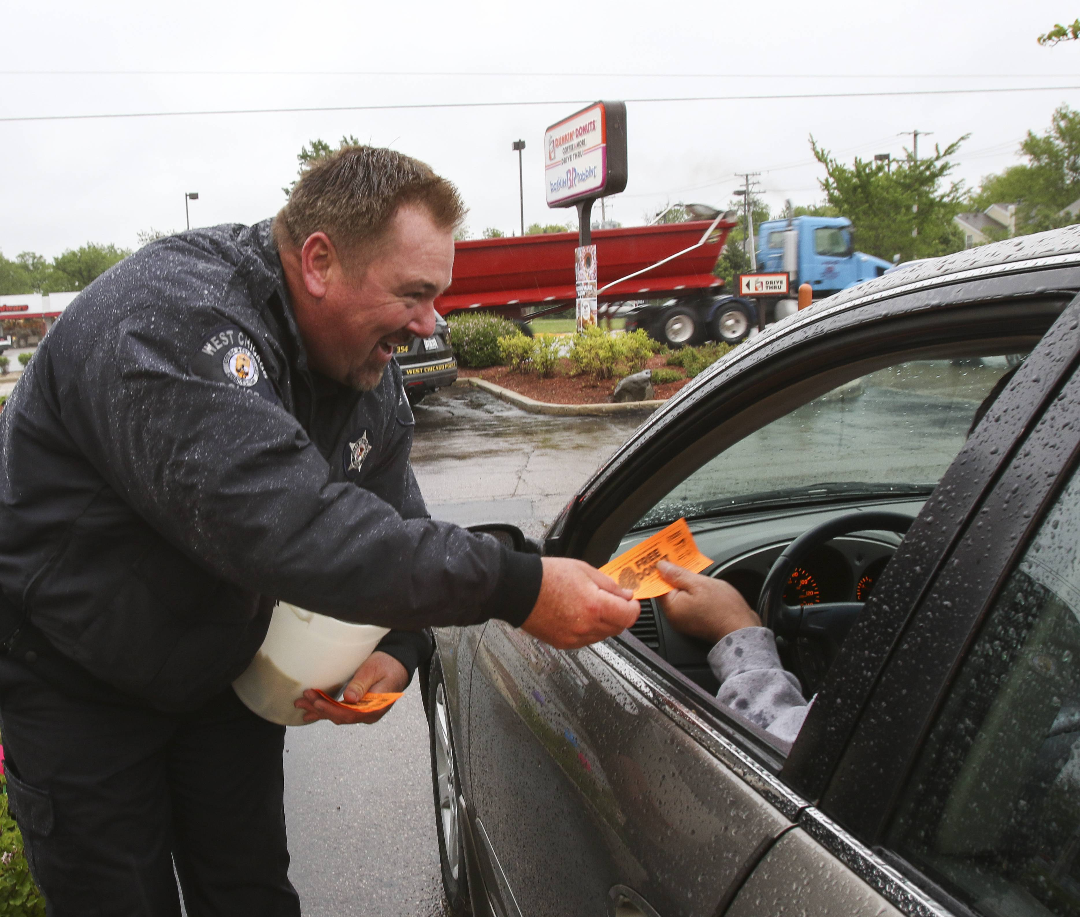 West Chicago Detective Robbie Peterson gives away a coupon for a doughnut as he helps collect money for Special Olympics during the annual Cop on a Rooftop fundraiser at Dunkin' Donuts in West Chicago.