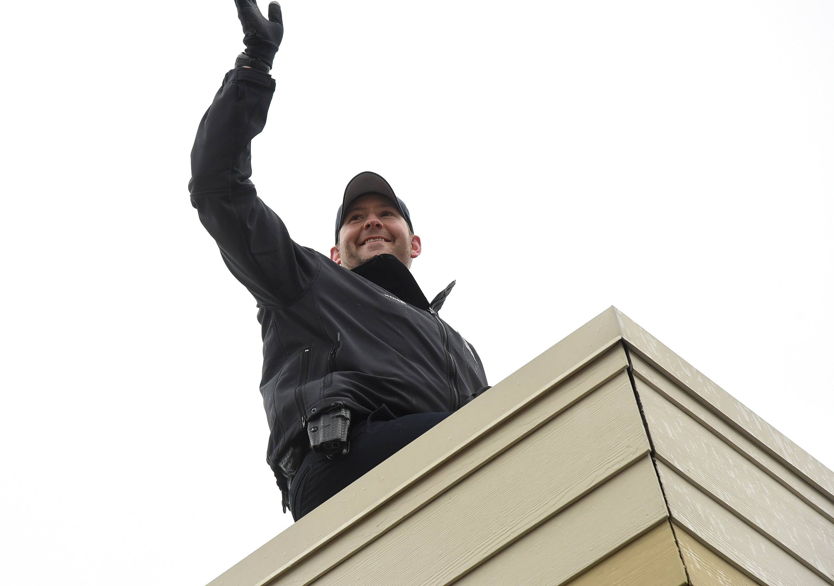 Barrington Police Officer Brian Hansen waves from atop the Barrington Dunkin' Donuts rooftop to support Special Olympics Illinois Friday.