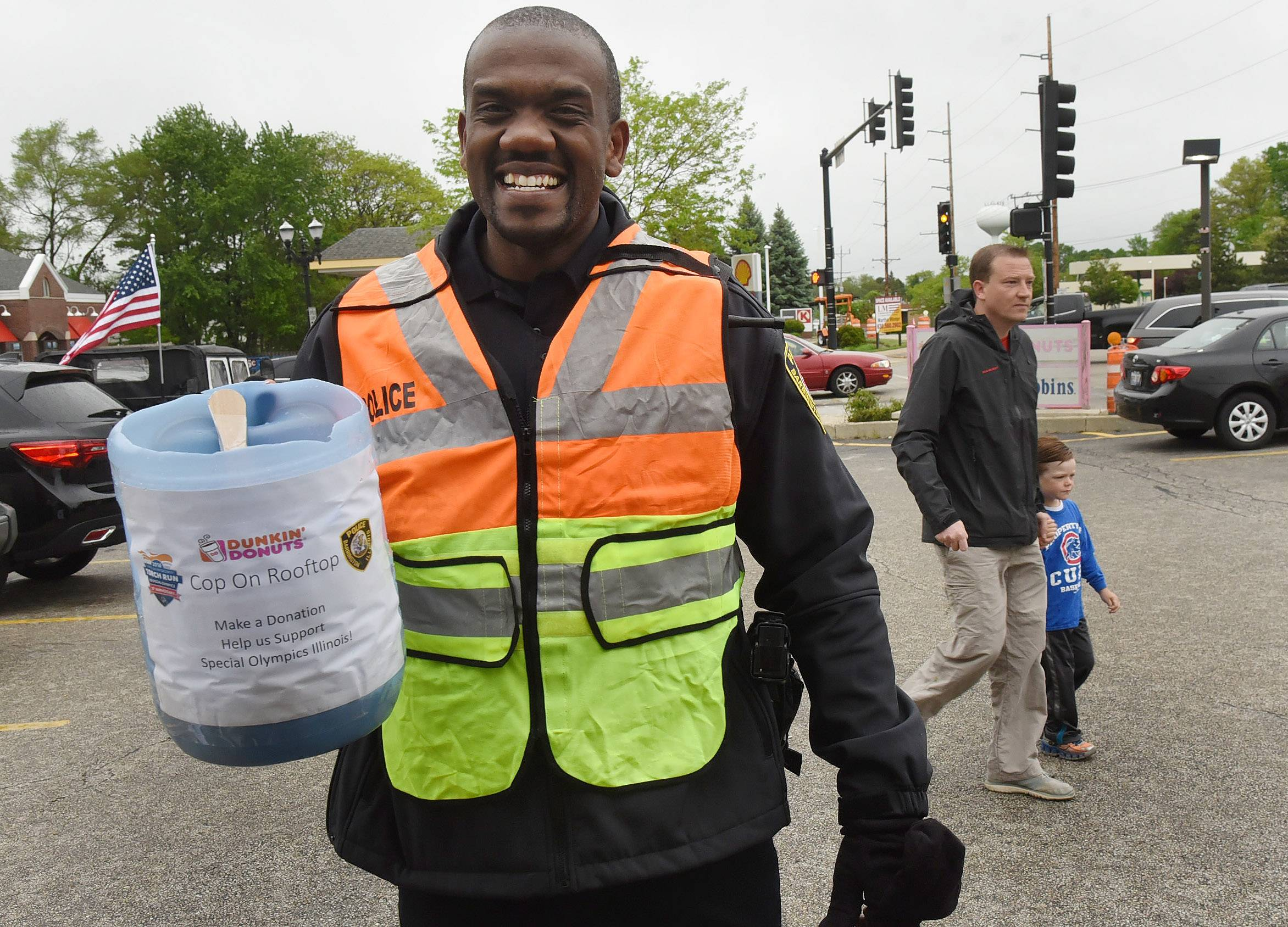 Barrinton Patrolman Hakeem Smith holds a jar of donations he accumulated at the corner of Route 14 and Lake Cook-Road by the Barrington Dunkin' Donuts to support Special Olympics Illinois Friday.