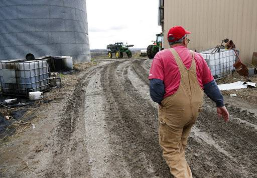 In this Tuesday, April 4, 2017, photo, Blake Hurst, a corn and soybean farmer and president of the Missouri Farm Bureau, walks to the tractor shed on his farm in Westboro, Mo. U.S. President Donald Trump has vowed to redo the North American Free Trade Agreement, but NAFTA has widened access to Mexican and Canadian markets, boosting U.S. farm exports and benefiting many farmers. Hurst says NAFTA has been good for his business and worries that he'll lose out in a renegotiation.