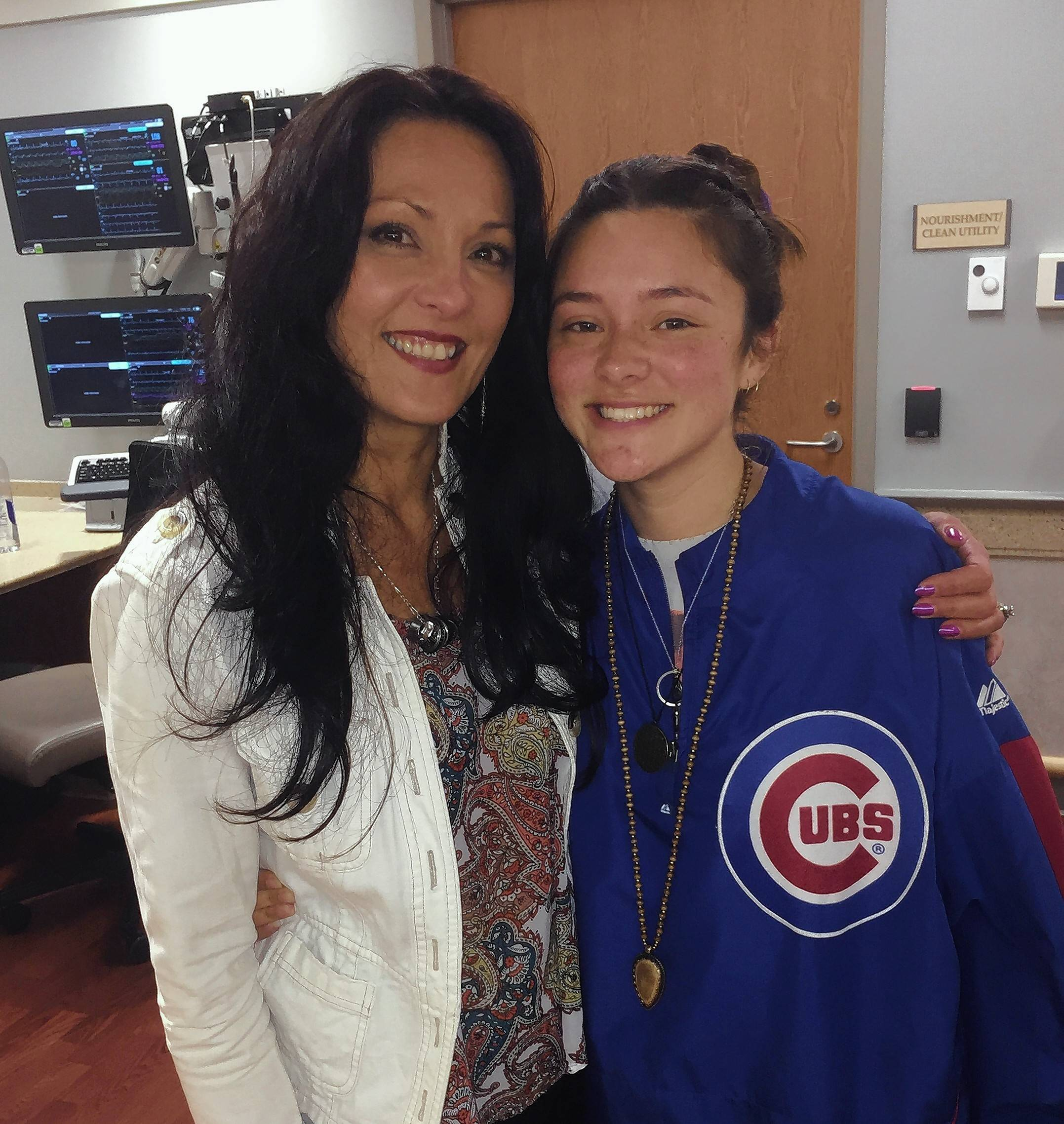 Isabella Griffin, right, wears her dad's Cubs jacket Friday at Edward Hospital in Naperville with her mom, Sara Case. Isabella's dad, Michael Case, is in critical condition at Edward after being shot while working as an Amtrak conductor.