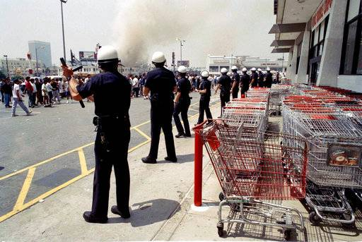 FILE - In this April 30, 1992 file photo Los Angeles police form a line to prevent a crowd from going into a building in a day of fires and looting in Los Angeles. After more than 25 years, authorities have identified the last remaining unidentified victim killed during the 1992 riots in Los Angeles. Los Angeles County coroner's spokesman Ed Winter identified the man Friday, May 19, 2017, as 18-year-old Armando Ortiz Hernandez. (AP Photo/Nick Ut,File)